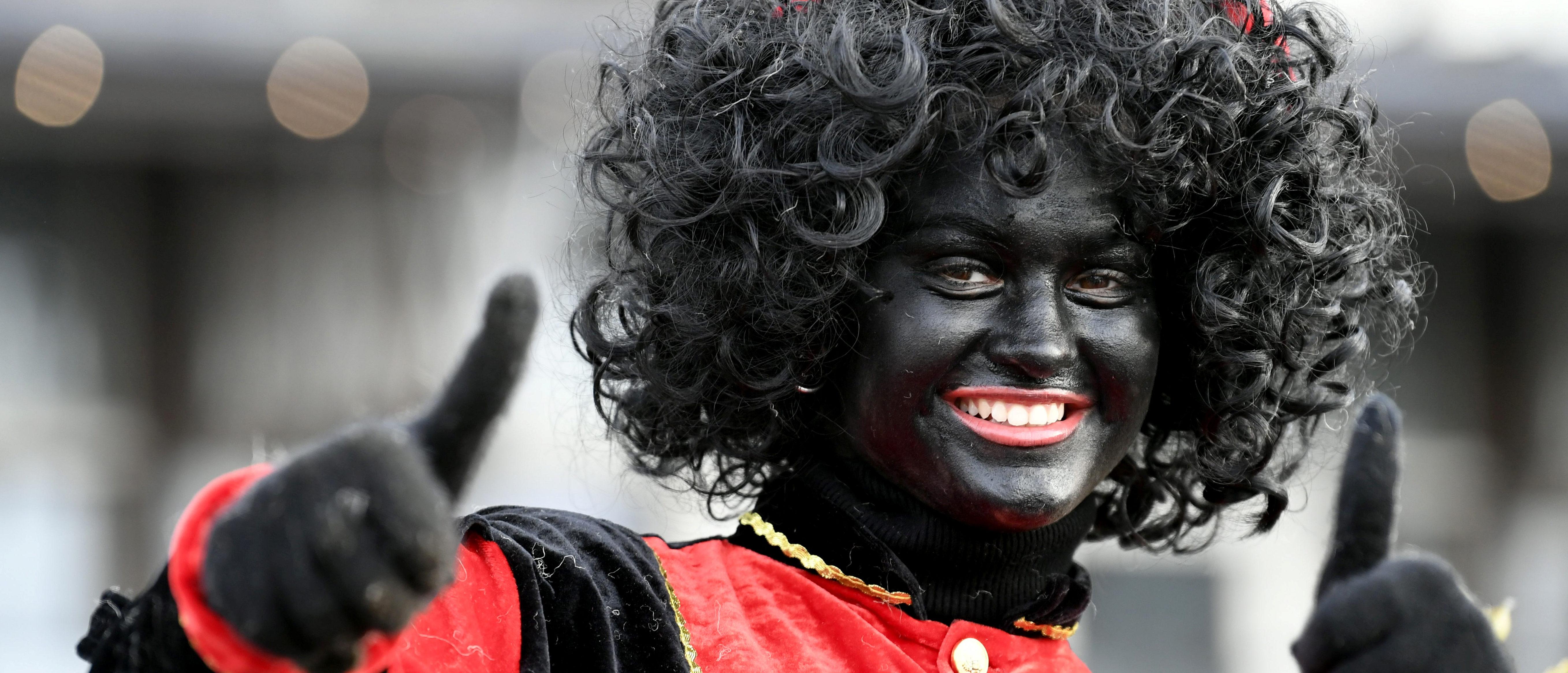 "An assistant of Saint Nicholas called ""Zwarte Piet"" (Black Pete) gestures as they arrive by boat at the harbour of Scheveningen, Netherlands, November 16, 2019. REUTERS/Piroschka van de Wouw - RC2BCD9I0ZSK"