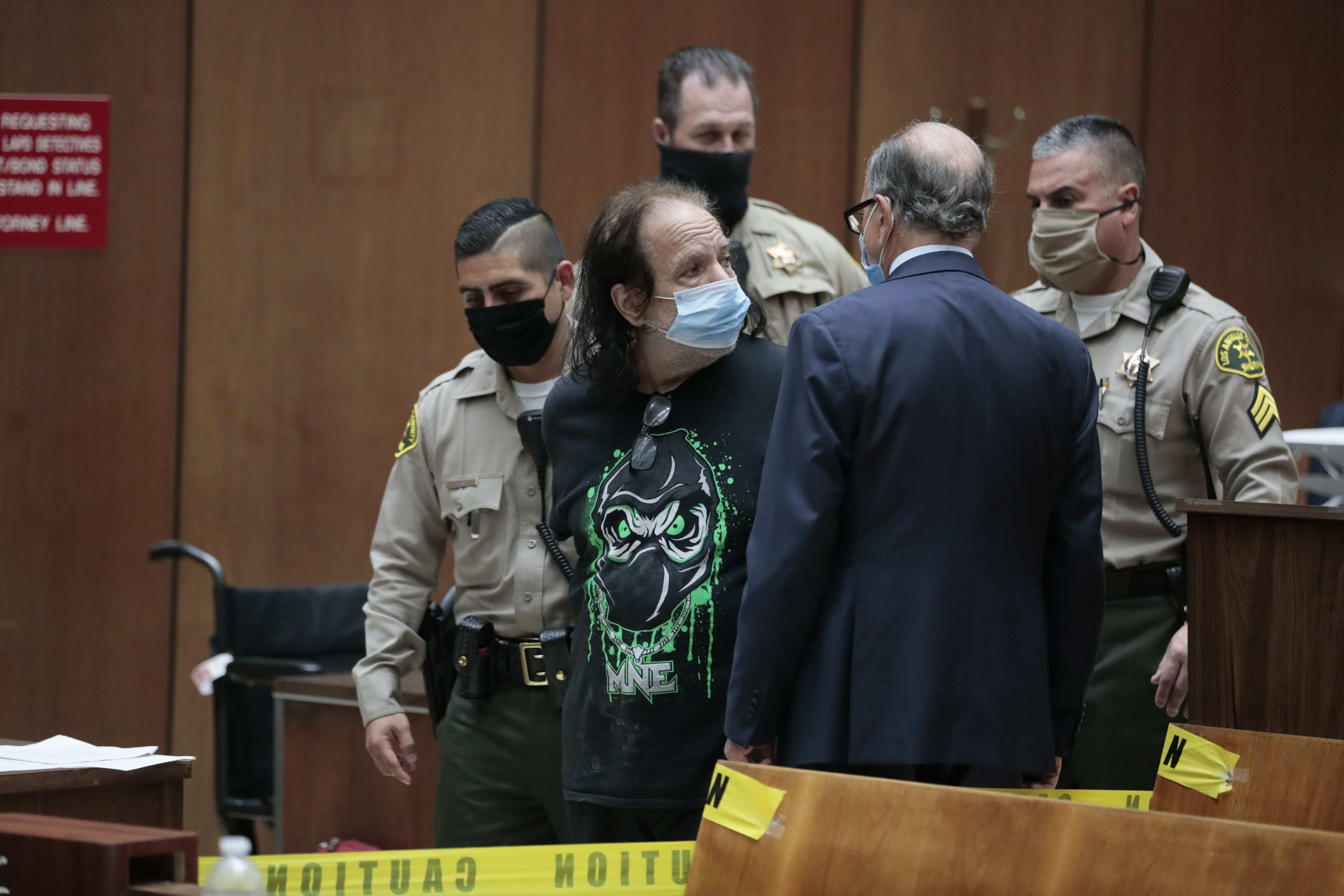 Adult film star Ron Jeremy (C) makes his first appearance in downtown Los Angeles Criminal Court, June 23, 2020. - Adult film star Ron Jeremy has been charged with raping three women and sexually assaulting a fourth, Los Angeles prosecutors said Tuesday. (Photo by ROBERT GAUTHIER/POOL/AFP via Getty Images)