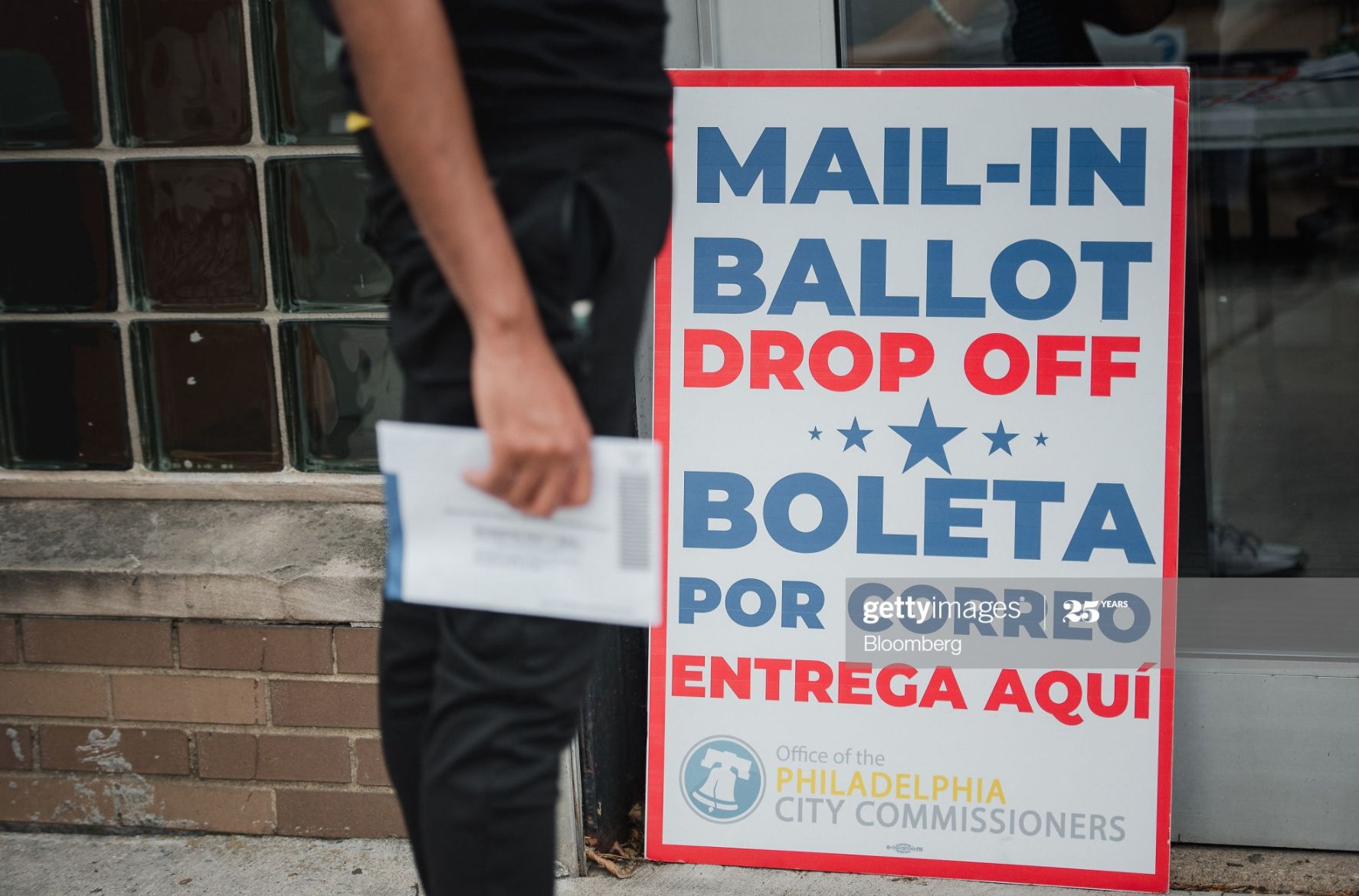 A voter waits to drop off his mail-in ballot at West Oak Lane Library in Philadelphia, Pennsylvania, U.S., on Tuesday, June 2, 2020. Amid the coronavirus pandemic, election officials encouraged voters in states including Indiana, Maryland, Montana, New Mexico, Iowa and South Dakota to cast ballots by mail or return them to voting centers or drop boxes before primary day.
