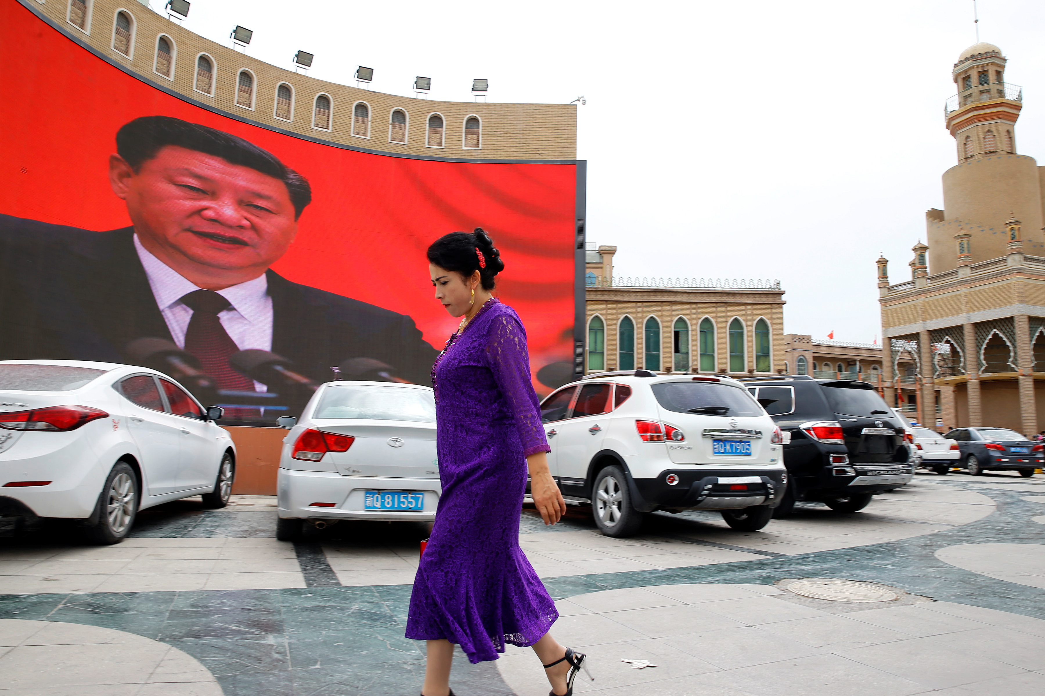 An ethnic Uighur woman walks in front of a giant screen with a picture of Chinese President Xi Jinping in the main city square in Kashgar in Xinjiang Uighur Autonomous Region, China September 6, 2018. The screen broadcasts a slideshow of images of Xi on loop, including propaganda images of his previous visit to Xinjiang. Picture taken September 6, 2018. To match Special Report MUSLIMS-CAMPS/CHINA REUTERS/Thomas Peter