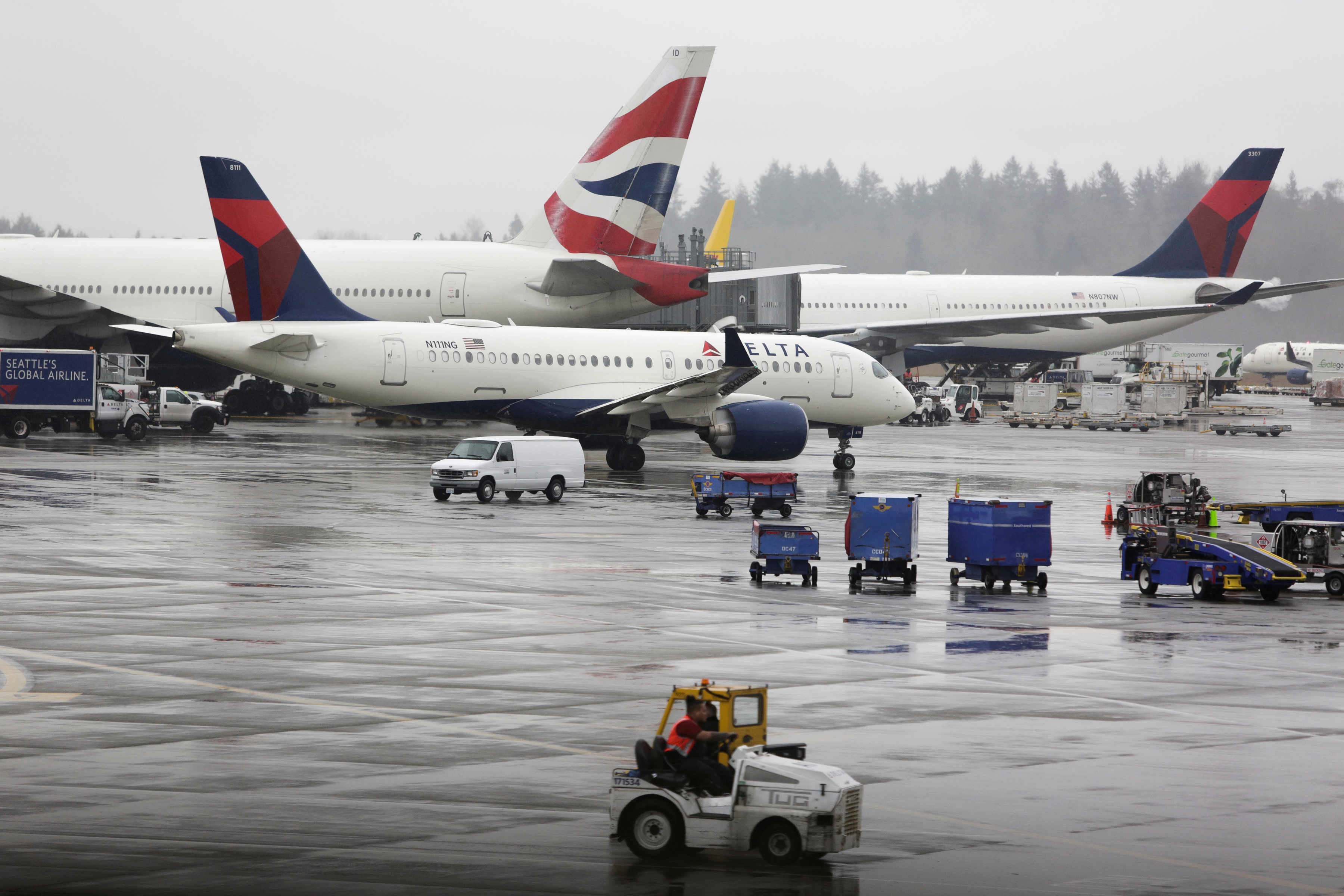 Delta Airlines planes and a British Airways plane (2nd L) are pictured at Seattle-Tacoma International Airport, on the day Delta CEO Ed Bastian told employees he was cutting 40% of capacity in the coming months, the largest in the airline's history, in addition to pursuing aid, in SeaTac, Washington, U.S. March 13, 2020. REUTERS/Jason Redmond