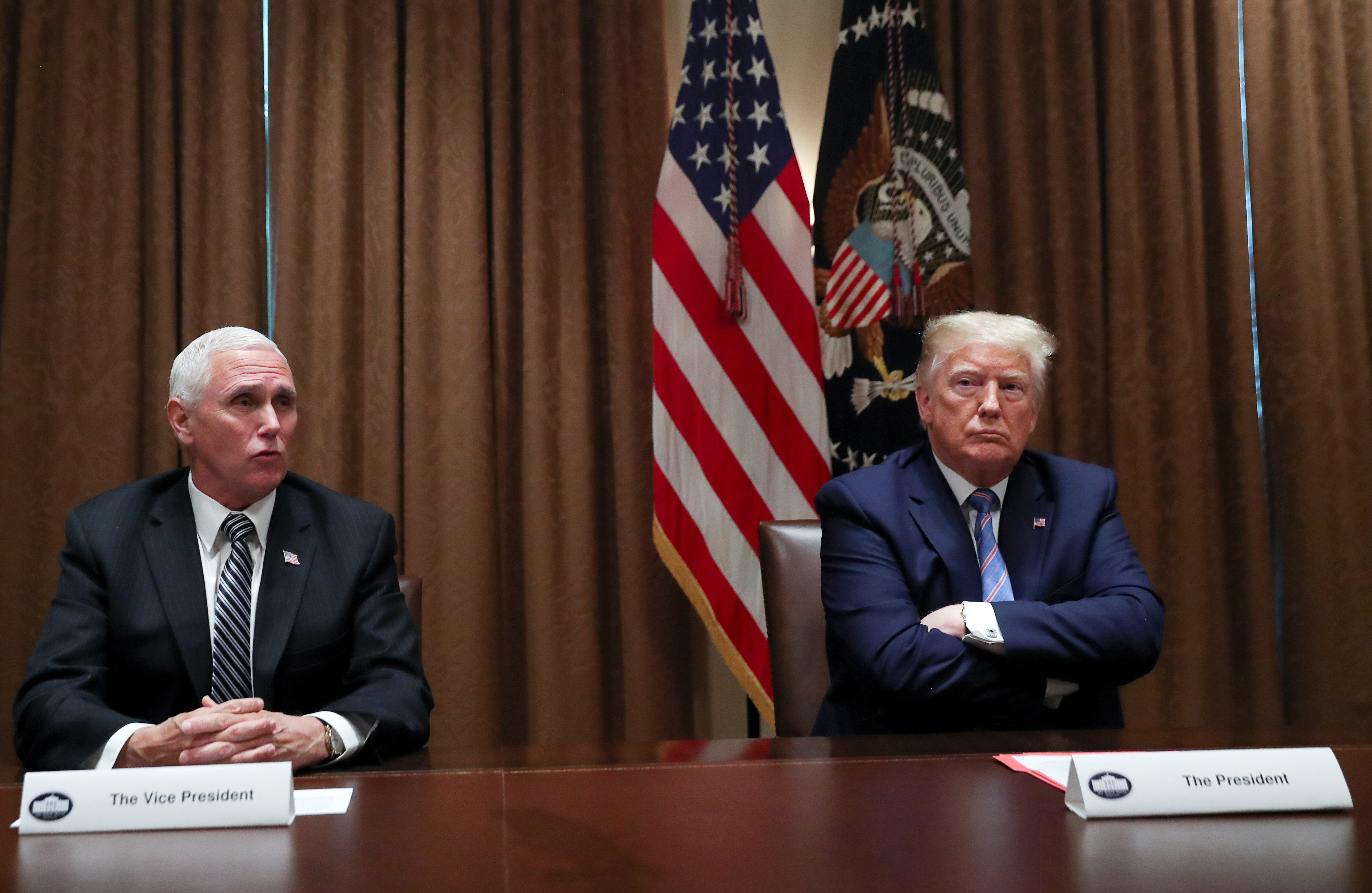 """FILE PHOTO: U.S. President Donald Trump listens to Vice President Mike Pence speak during a roundtable discussion on """"America's seniors"""" in the Cabinet Room at the White House in Washington, U.S., June 15, 2020. REUTERS/Leah Millis"""