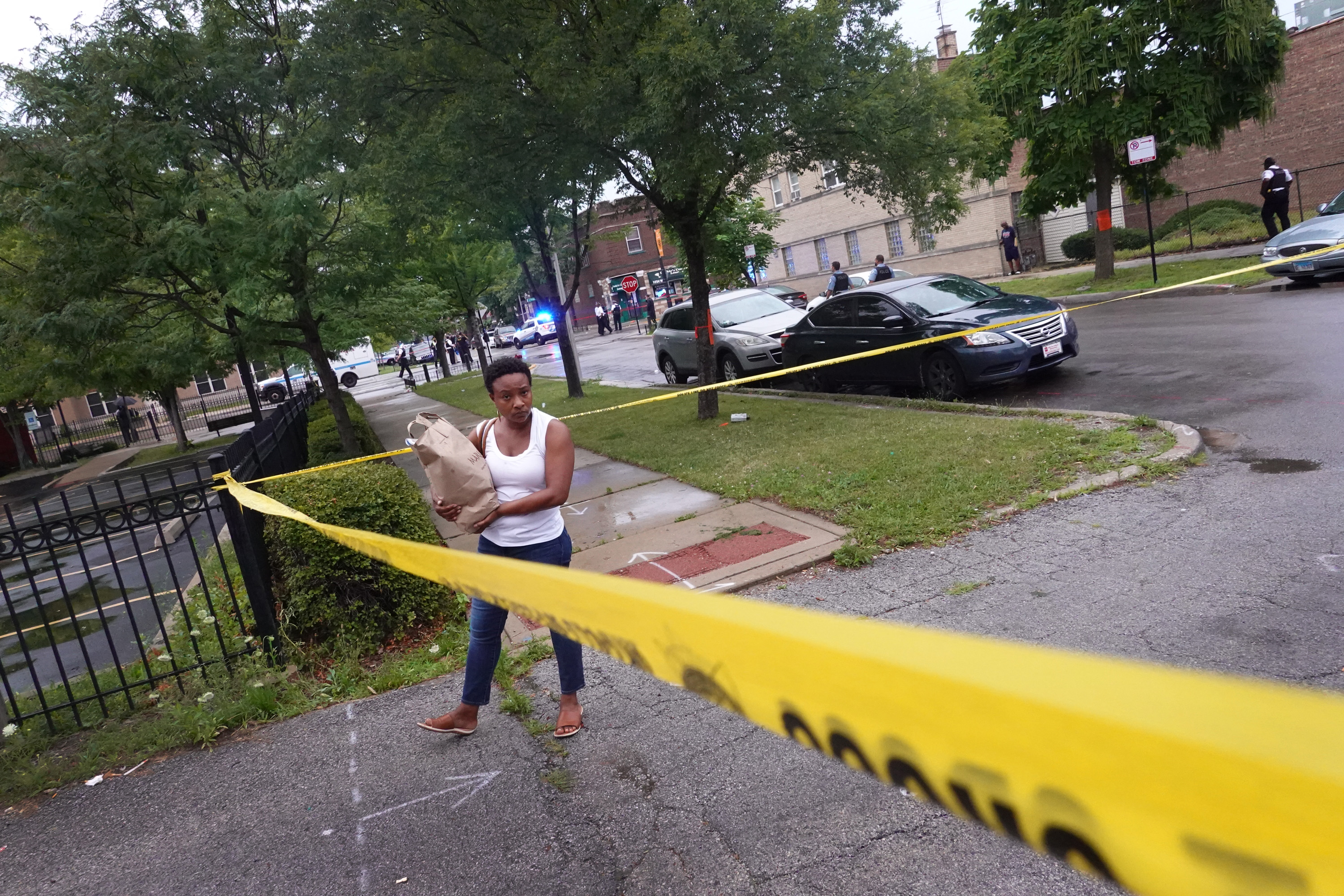 CHICAGO, ILLINOIS - JULY 21: A resident stands inside of police tape as Chicago police secure the scene of a shooting in the Auburn Gresham neighborhood on July 21, 2020 in Chicago, Illinois. At least 14 people were transported to area hospitals after several gunmen opened fire on mourners standing outside of a funeral home. More than 2000 people have been shot and more than 400 have been murdered in Chicago so far this year. (Photo by Scott Olson/Getty Images)