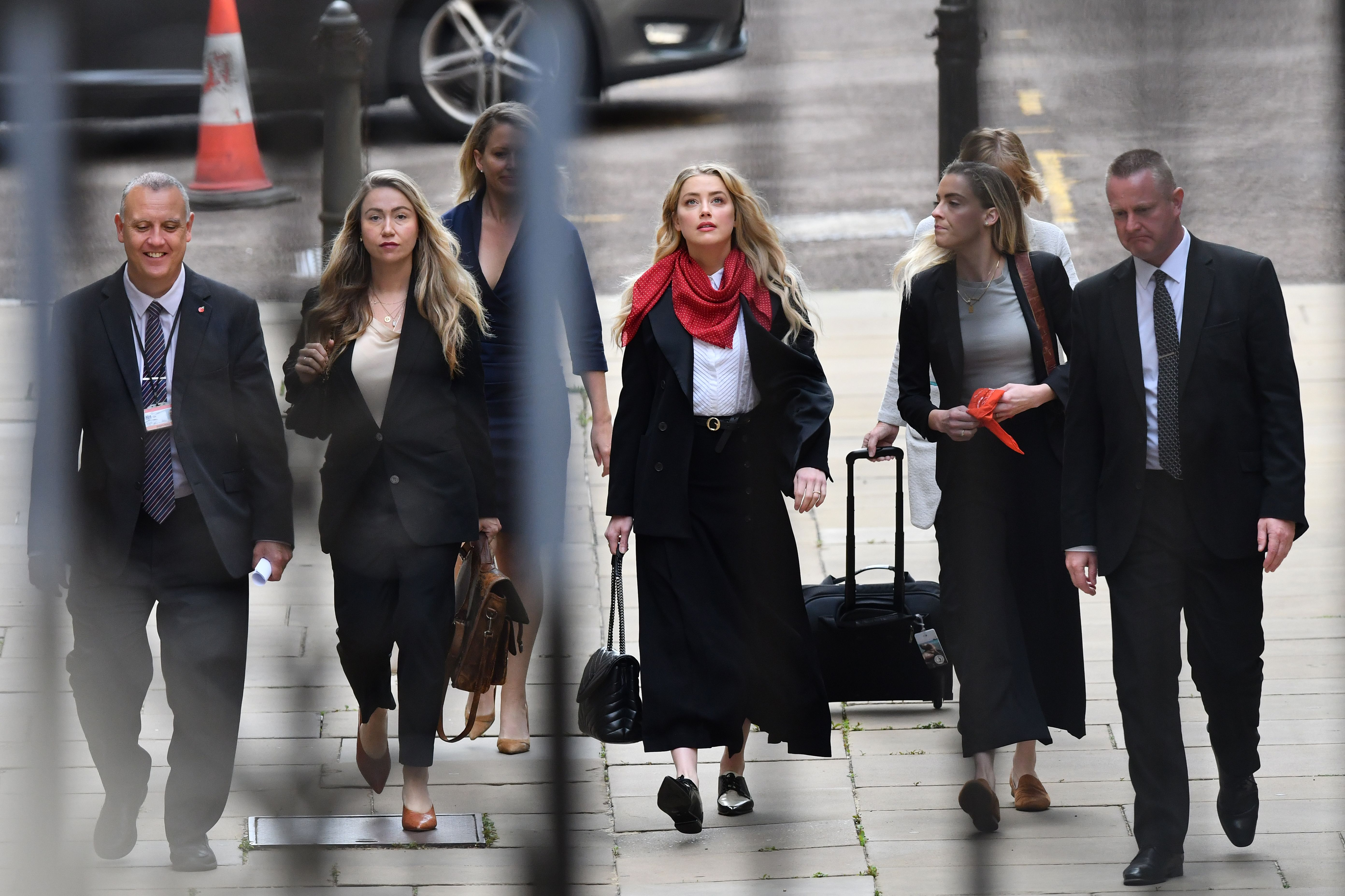 """US actress Amber Heard (C) arrives on the sixth day of the libel trial by her former husband US actor Johnny Depp against News Group Newspapers (NGN), at the High Court in London, on July 14, 2020. - Depp is suing the publishers of The Sun and the author of the article for the claims that called him a """"wife-beater"""" in April 2018. (Photo by JUSTIN TALLIS/AFP via Getty Images)"""