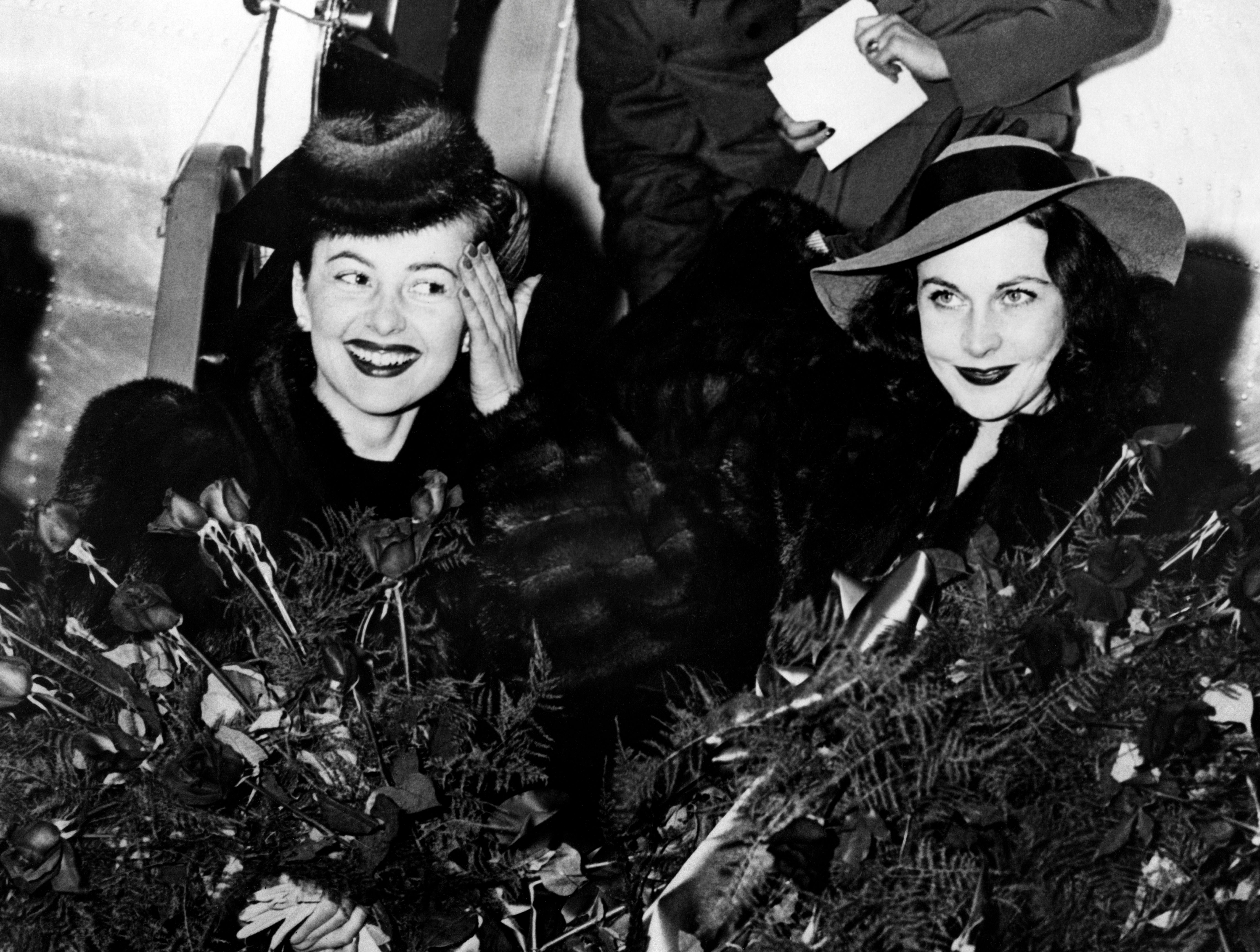 "US actress Olivia de Havilland (L) and Vivien Leigh pictured as they stepped from a plane upon their arrival in Atlanta for the premiere of ""Gone with the wind"" on December 1939. (Photo by -/ACME/AFP via Getty Images)"