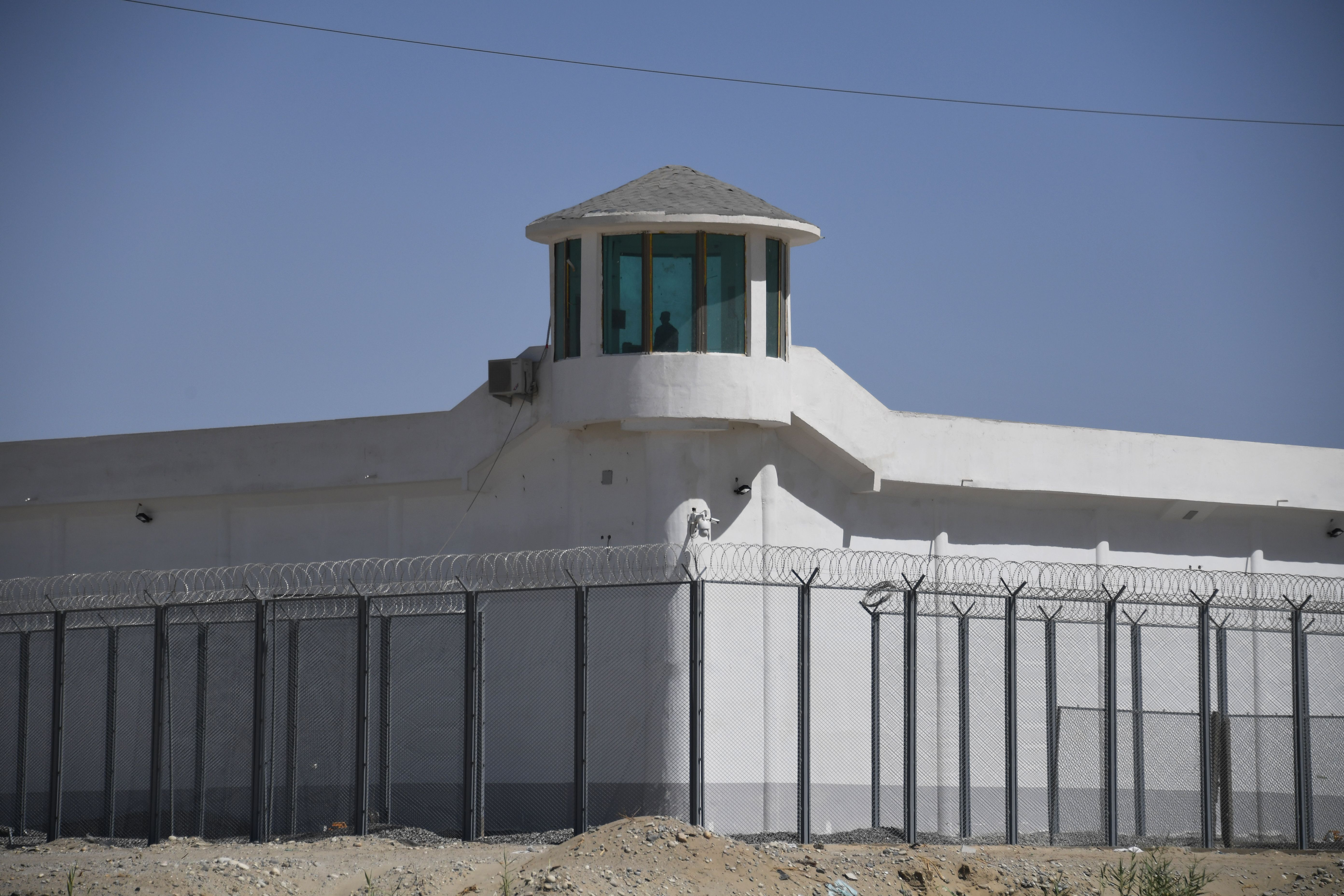 """TOPSHOT - This photo taken on May 31, 2019 shows a watchtower on a high-security facility near what is believed to be a re-education camp where mostly Muslim ethnic minorities are detained, on the outskirts of Hotan, in China's northwestern Xinjiang region. - As many as one million ethnic Uighurs and other mostly Muslim minorities are believed to be held in a network of internment camps in Xinjiang, but China has not given any figures and describes the facilities as """"vocational education centres"""" aimed at steering people away from extremism. (Photo by GREG BAKER / AFP) / TO GO WITH AFP STORY CHINA-XINJIANG-MEDIA-RIGHTS-PRESS,FOCUS BY EVA XIAO (Photo credit should read GREG BAKER/AFP via Getty Images)"""