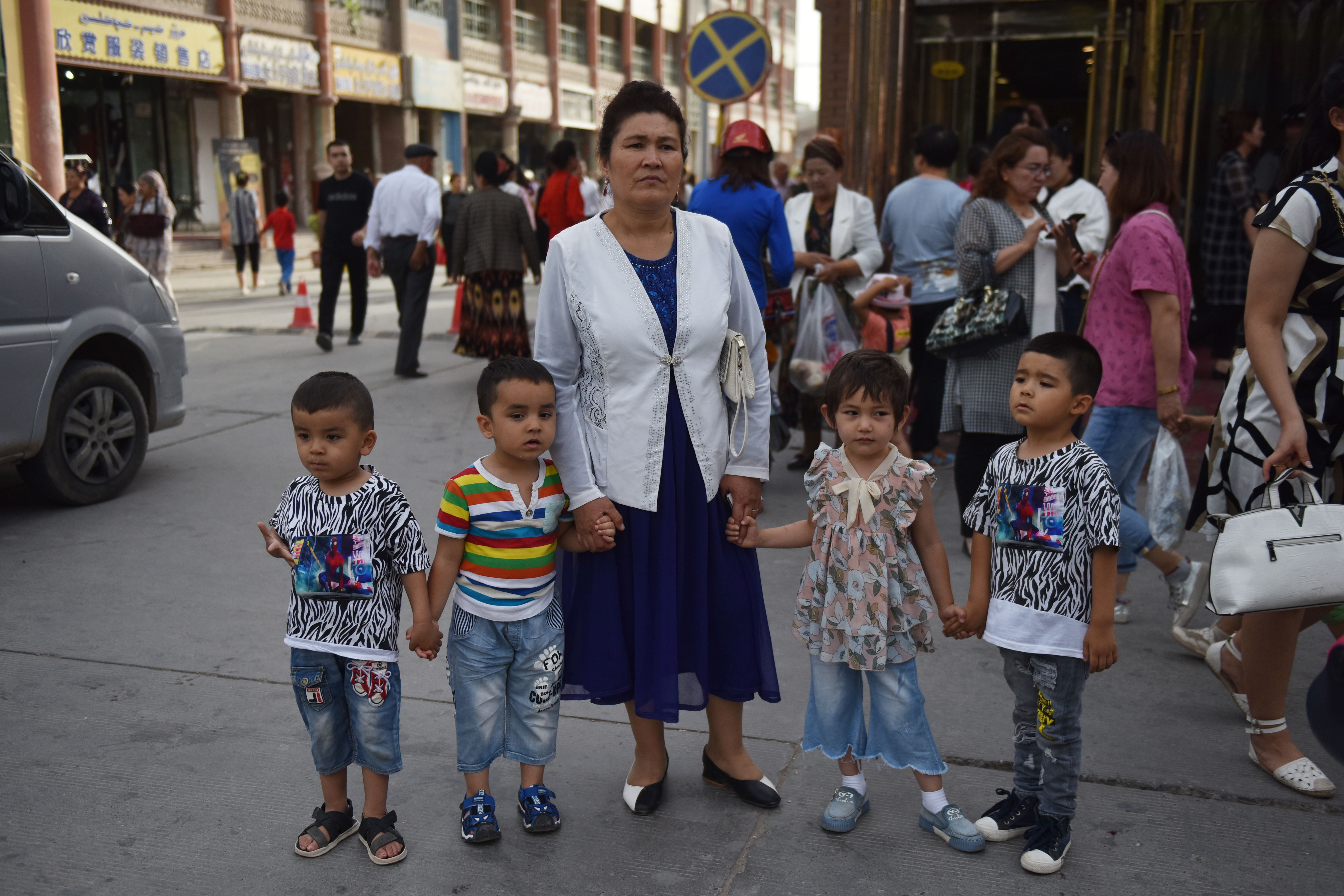 This photo taken on June 4, 2019 shows a Uighur woman waiting with children on a street in Kashgar in China's northwest Xinjiang region. (GREG BAKER/AFP via Getty Images)