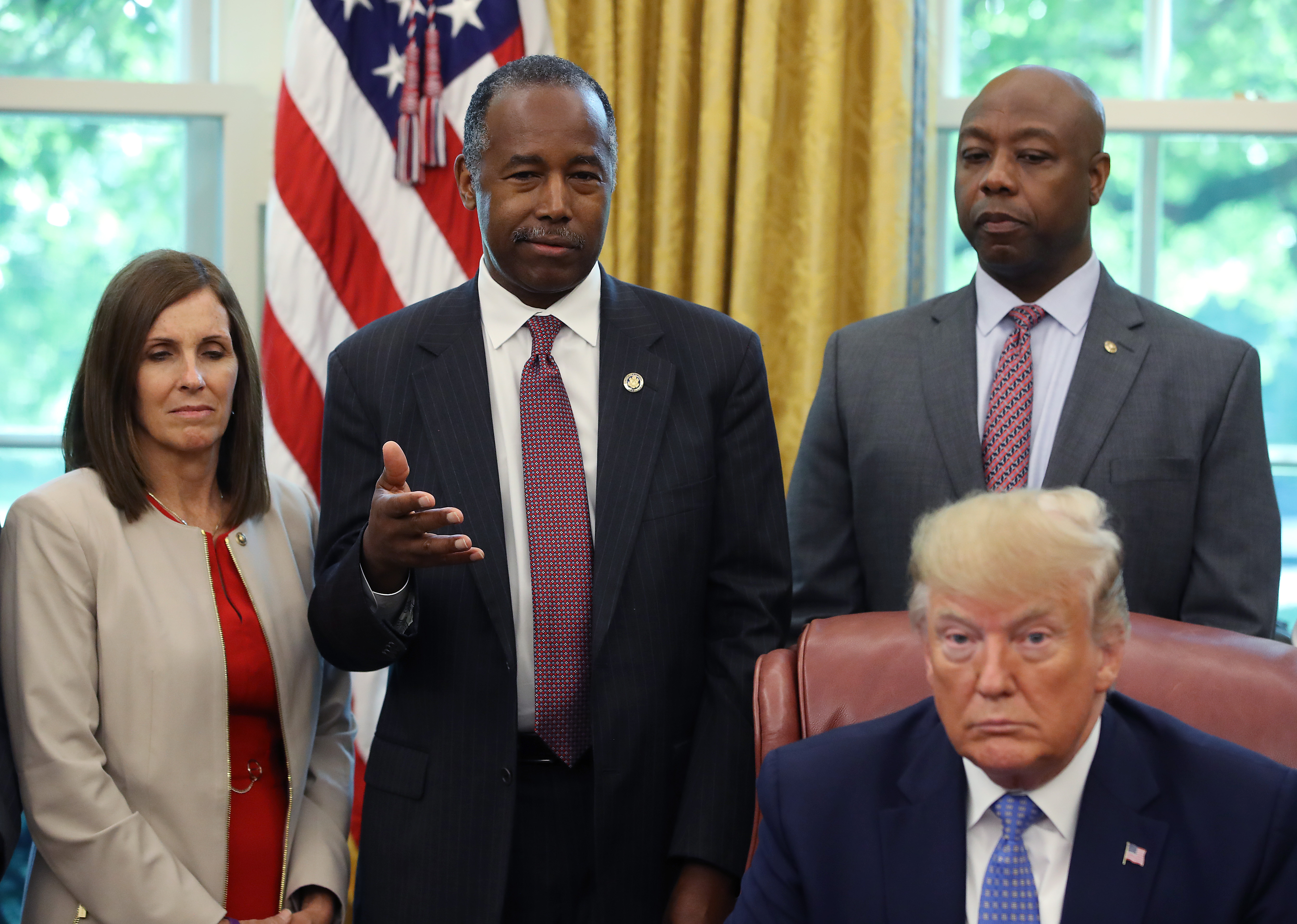 WASHINGTON, DC - JUNE 25: Housing and Urban Development Secretary Ben Carson (2L) speaks before U.S. President Donald Trump signed an executive order establishing a White House Council on eliminating regulatory barriers to affordable housing, in the Oval Office at the White House on June 25, 2019 in Washington, DC. DC. The council, which will be made up of members of eight federal agencies, will reportedly be tasked with easing local barriers to the private sector of creating housing, according to published reports. Also picture are Sen. Martha McSally (R-AZ) (L) and Sen. Tim Scott (R-SC). (Photo by Mark Wilson/Getty Images)