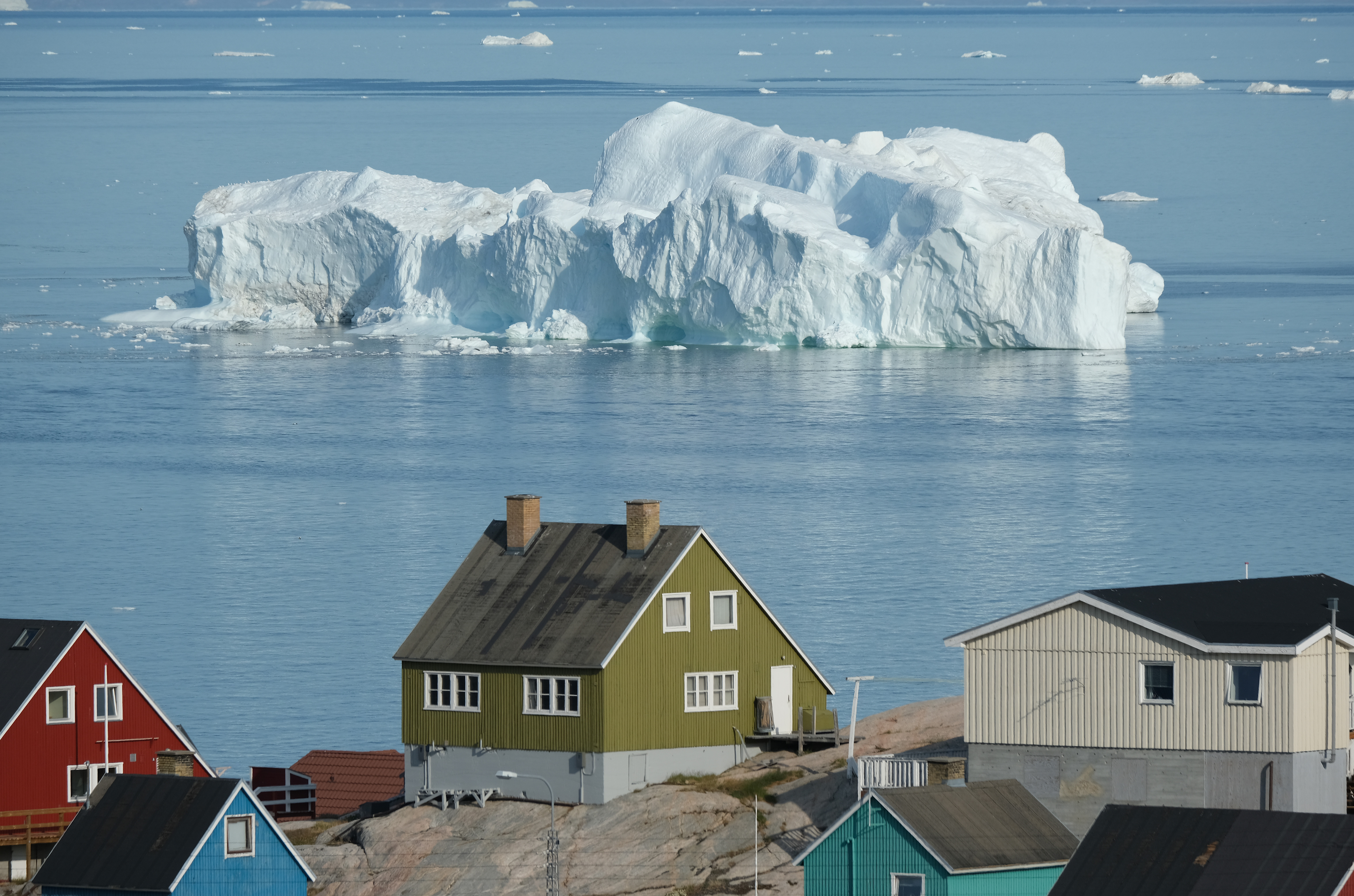 An iceberg floats in Disko Bay behind houses during unseasonably warm weather on July 30, 2019 in Ilulissat, Greenland. The Sahara heat wave that recently sent temperatures to record levels in parts of Europe is arriving in Greenland. Climate change is having a profound effect in Greenland, where over the last several decades summers have become longer and the rate that glaciers and the Greenland ice cap are retreating has accelerated. (Photo by Sean Gallup/Getty Images)