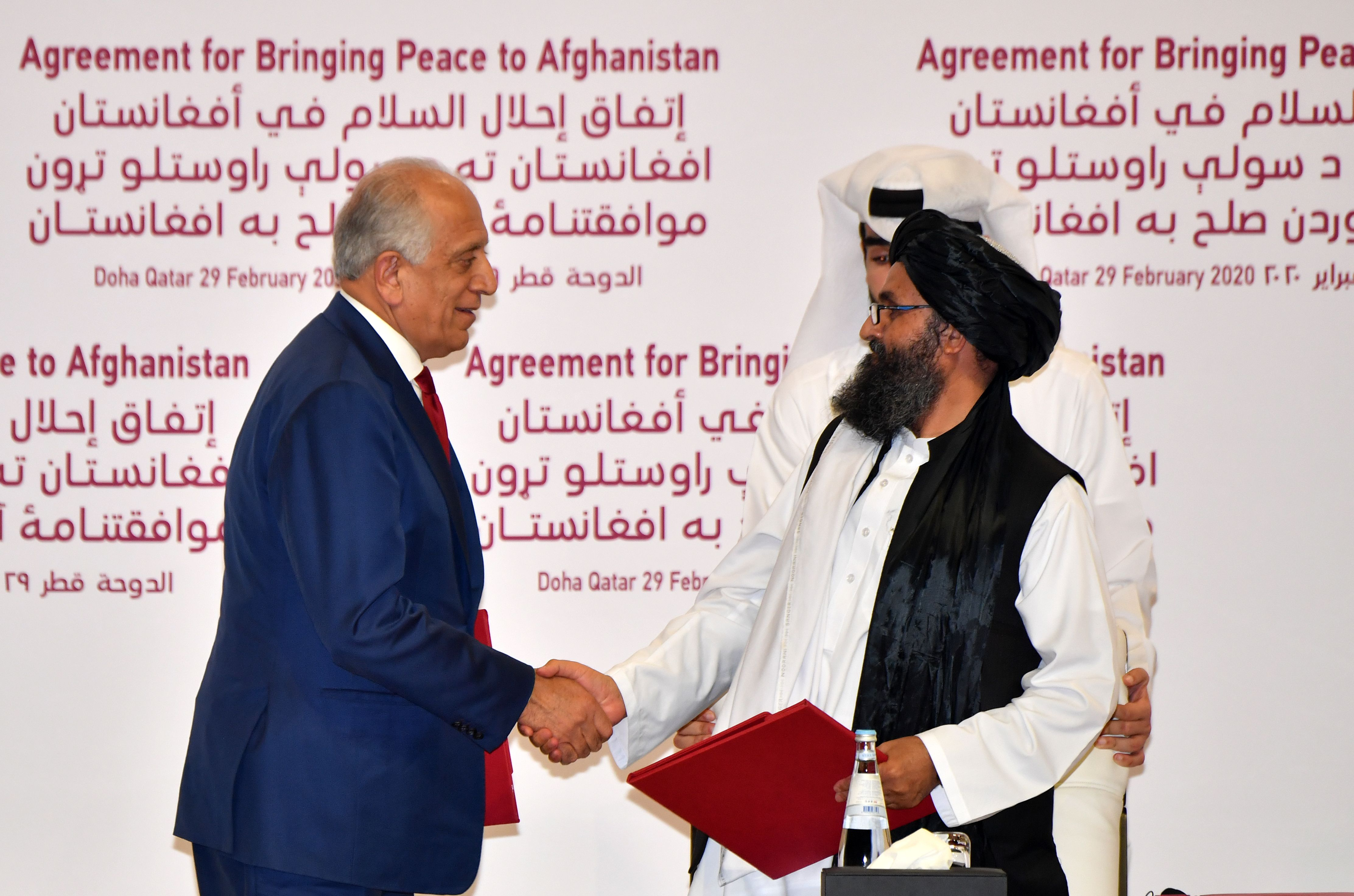 TOPSHOT - (L to R) US Special Representative for Afghanistan Reconciliation Zalmay Khalilzad and Taliban co-founder Mullah Abdul Ghani Baradar shake hands after signing a peace agreement during a ceremony in the Qatari capital Doha on February 29, 2020 - The United States signed a landmark deal with the Taliban, laying out a timetable for a full troop withdrawal from Afghanistan within 14 months as it seeks an exit from its longest-ever war. (Photo by Giuseppe CACACE / AFP) (Photo by GIUSEPPE CACACE/AFP via Getty Images)