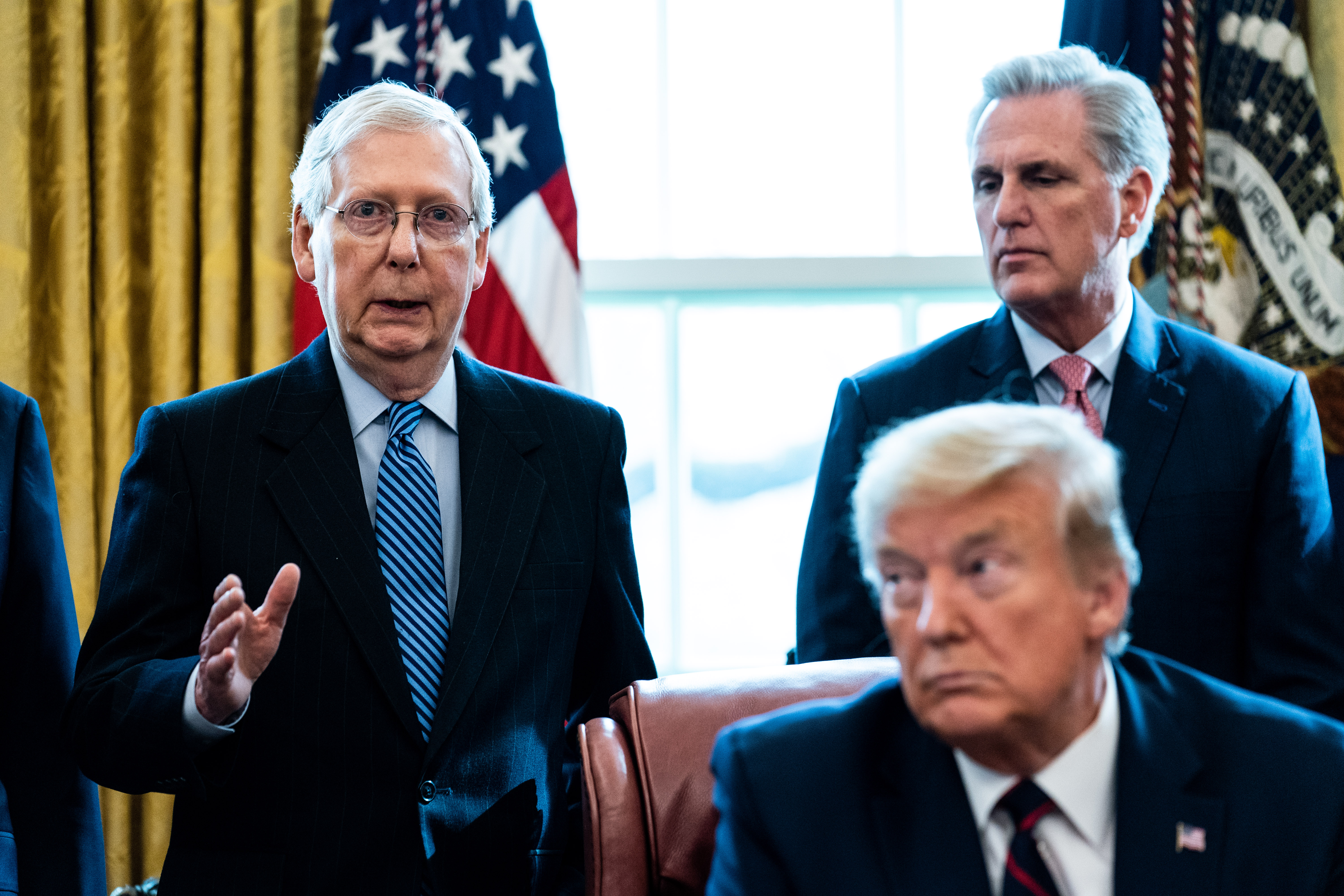 WASHINGTON, DC - MARCH 27: (L-R) Senate Majority Leader Mitch McConnell (R-KY) speaks as House Minority Leader Kevin McCarthy (R-CA) U.S. President Donald Trump listen during a signing ceremony for H.R. 748, the CARES Act in the Oval Office of the White House on March 27, 2020 in Washington, DC. Earlier on Friday, the U.S. House of Representatives approved the $2 trillion stimulus bill that lawmakers hope will battle the the economic effects of the COVID-19 pandemic. (Photo by Erin Schaff-Pool/Getty Images)
