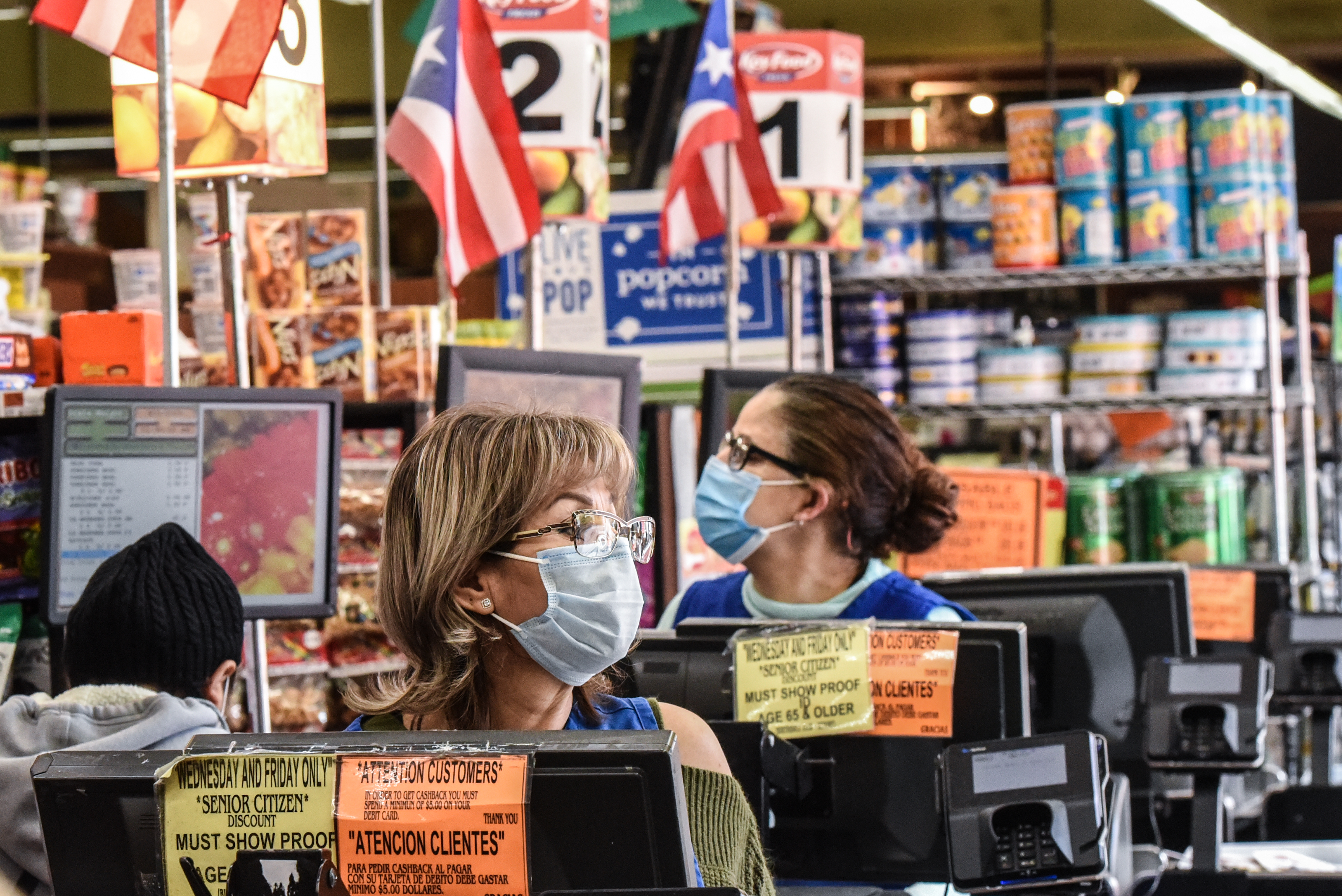 NEW YORK, NY - APRIL 02 : Cashiers wearing protective masks work in a grocery store in the Bushwick neighborhood of Brooklyn on April 2, 2020 in New York City. New York City is in its second week of lock down due to the coronavirus. (Photo by Stephanie Keith/Getty Images)
