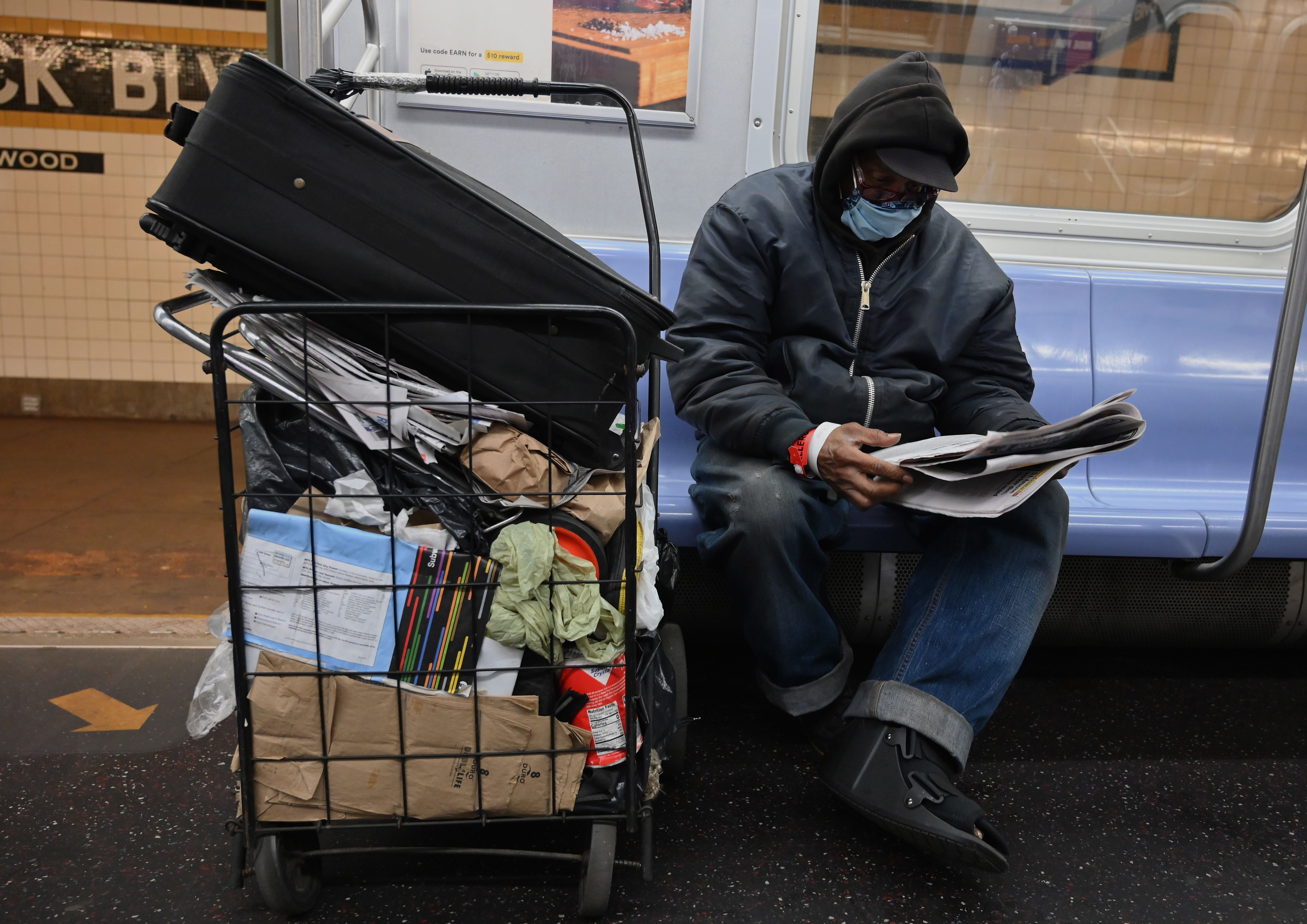 Damon, 67 who is homeless reads a newspaper on a subway train on May 7, 2020 in New York City. (Photo by ANGELA WEISS/AFP via Getty Images)