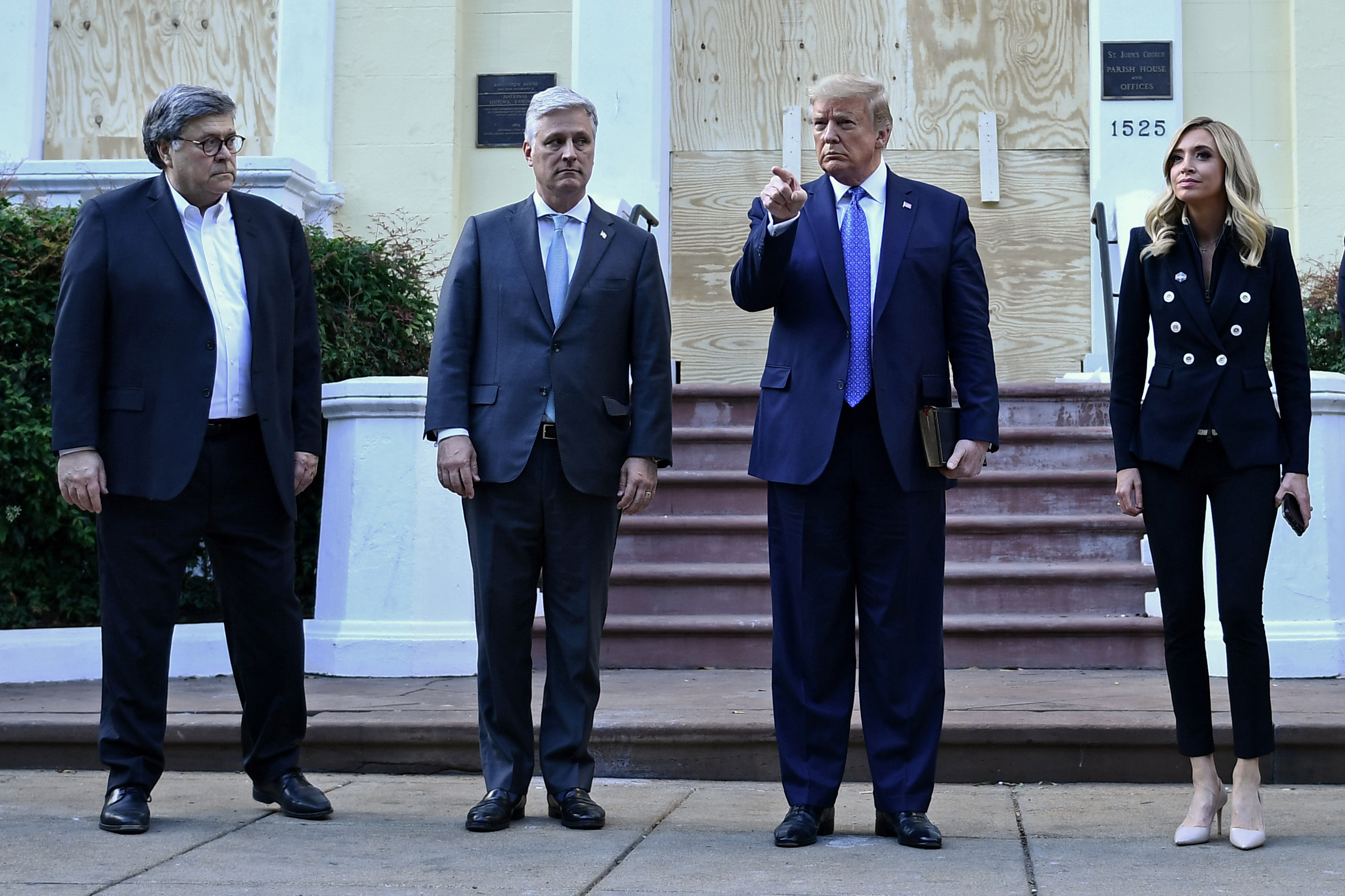 US President Donald Trump holds up a Bible as he gestures, alongside US Attorney General William Barr (L), White House national security adviser Robert O'Brien (2nd-L) and White House press secretary Kayleigh McEnany, outside of St John's Episcopal church across Lafayette Park in Washington, DC on June 1, 2020. - US President Donald Trump was due to make a televised address to the nation on Monday after days of anti-racism protests against police brutality that have erupted into violence. The White House announced that the president would make remarks imminently after he has been criticized for not publicly addressing in the crisis in recent days. (Photo by BRENDAN SMIALOWSKI/AFP via Getty Images)