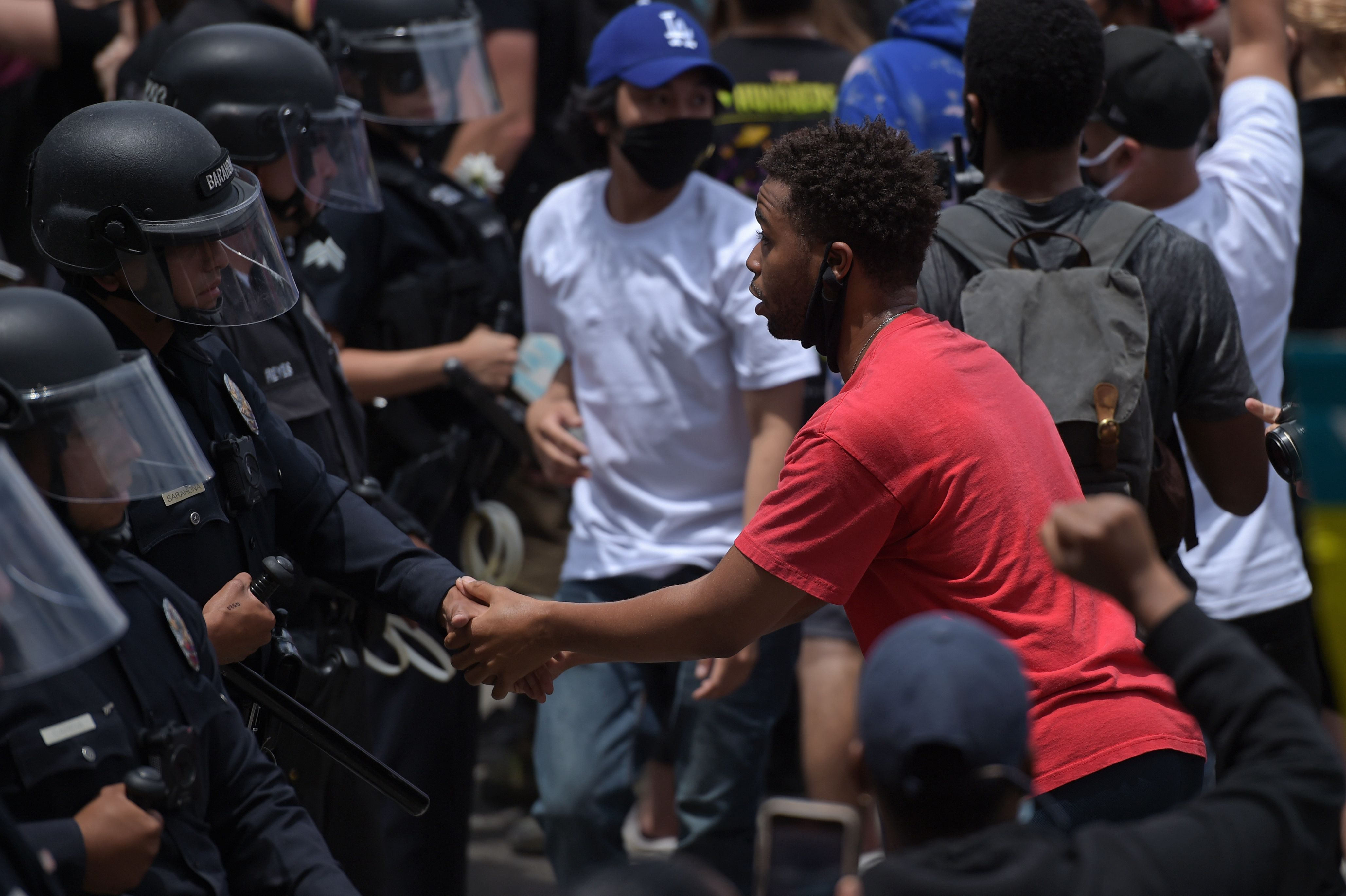 A protester shakes hands with an LAPD officer during a demonstration over the death of George Floyd in Hollywood, California on June 2, 2020. (Photo: Agustin Paullier/AFP via Getty Images)