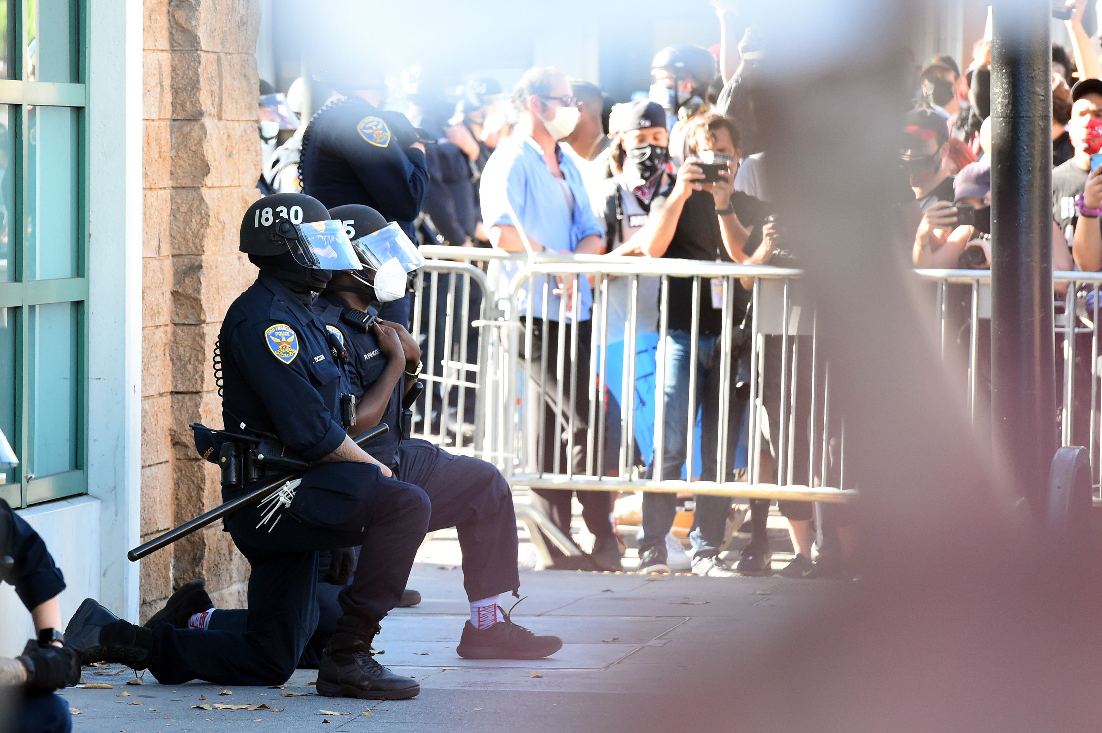 """San Francisco police officers kneel after a crowd of protesters called for them to """"take a knee"""" in front of a police station in San Francisco, California on June 3, 2020. (Photo: Josh Edelson/AFP via Getty Images)"""
