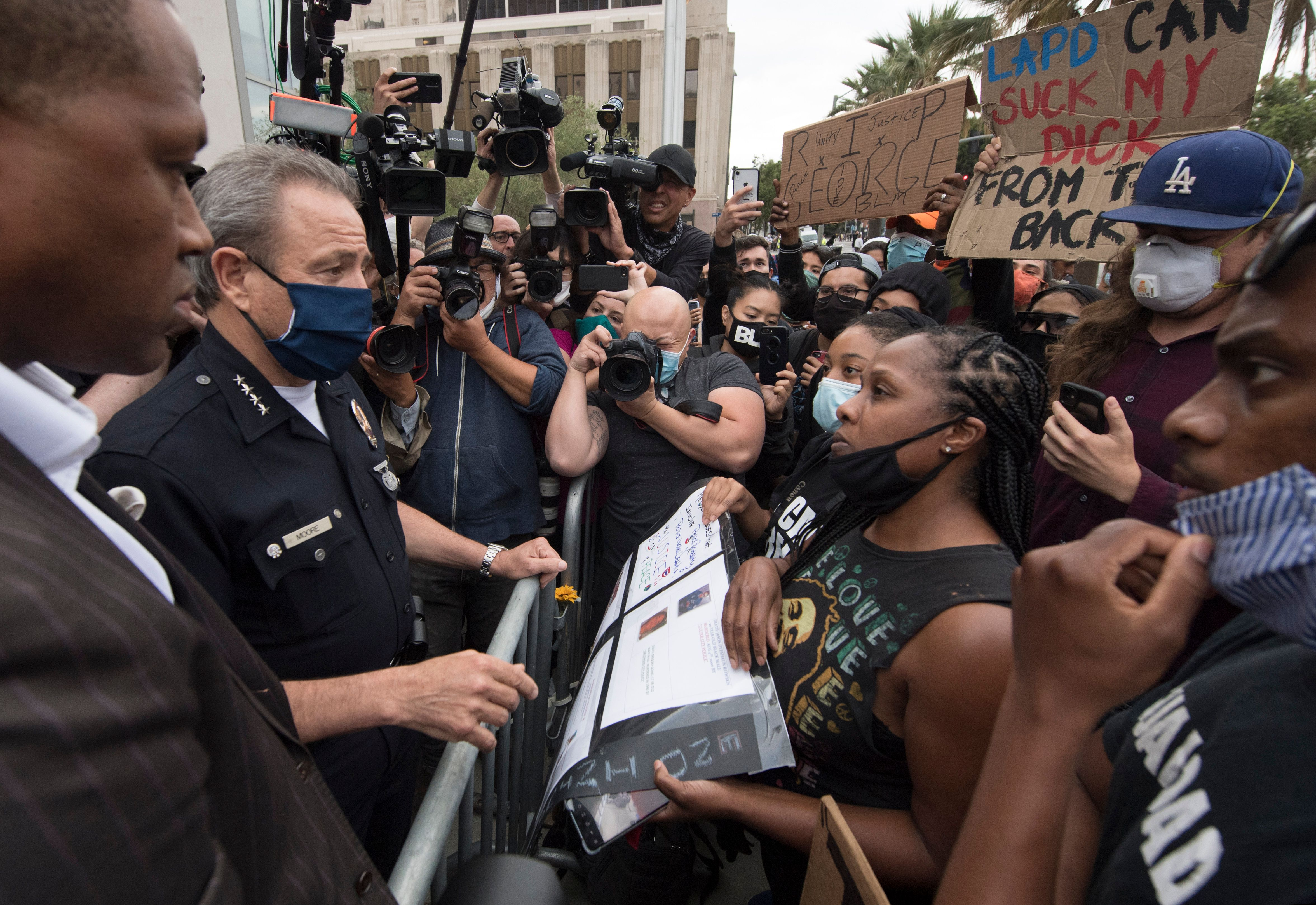 Los Angeles Police Chief Michel Moore talks with Black Lives Matter members after a vigil for George Floyd at police headquarters on June 5, 2020. (Photo: Mark Ralston/AFP via Getty Images)