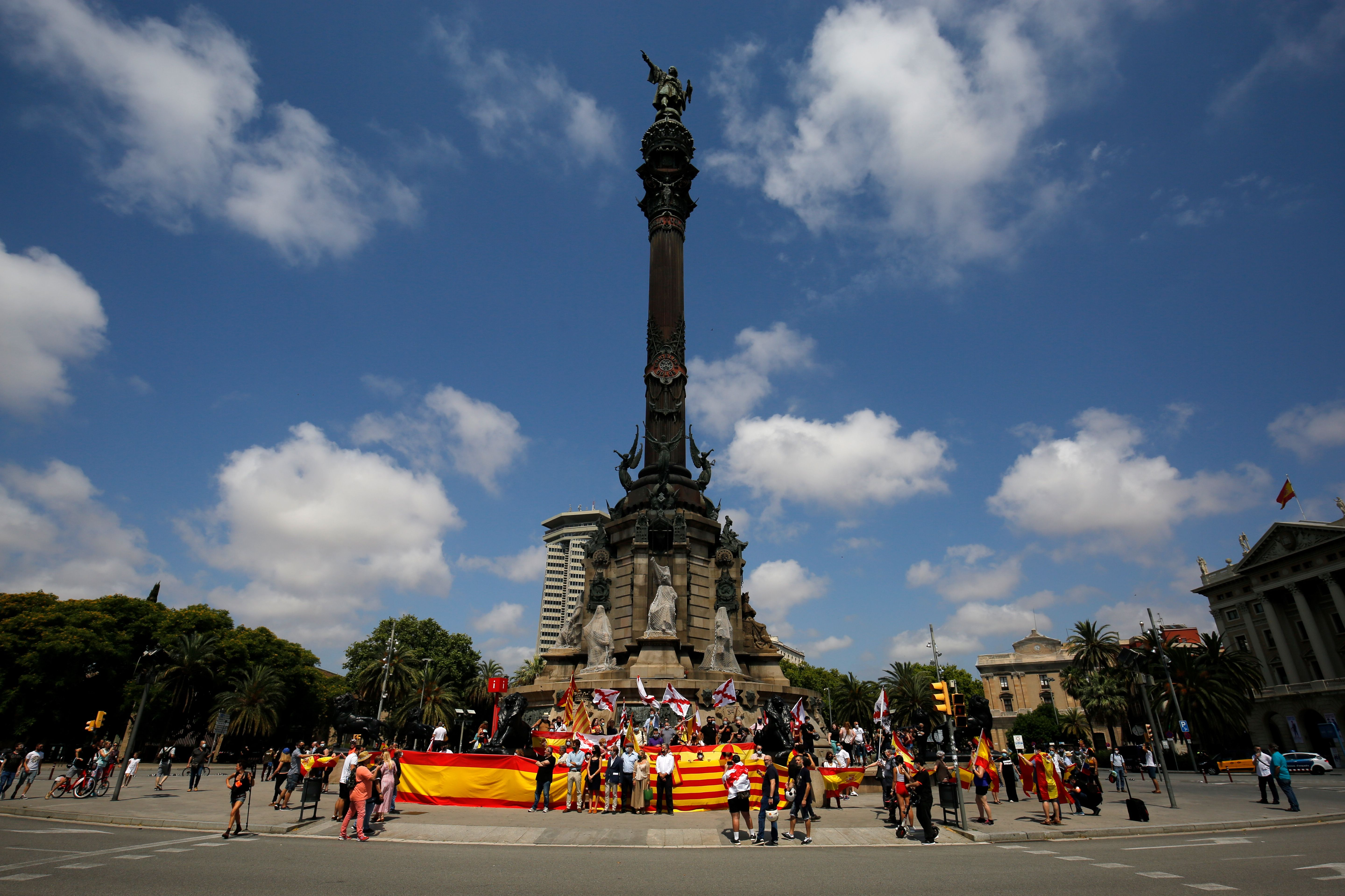 Protesters hold Spanish and Catalan Senyera flags along with Cross of Burgundy flags during a demonstration organised by Spain's far-right Vox party to preserve a statue of Christopher Columbus in Barcelona on June 27, 2020 as statues of slave traders and colonial figures tumble worldwide in a wave of anger against racism. (Photo by Pau Barrena/AFP via Getty Images)