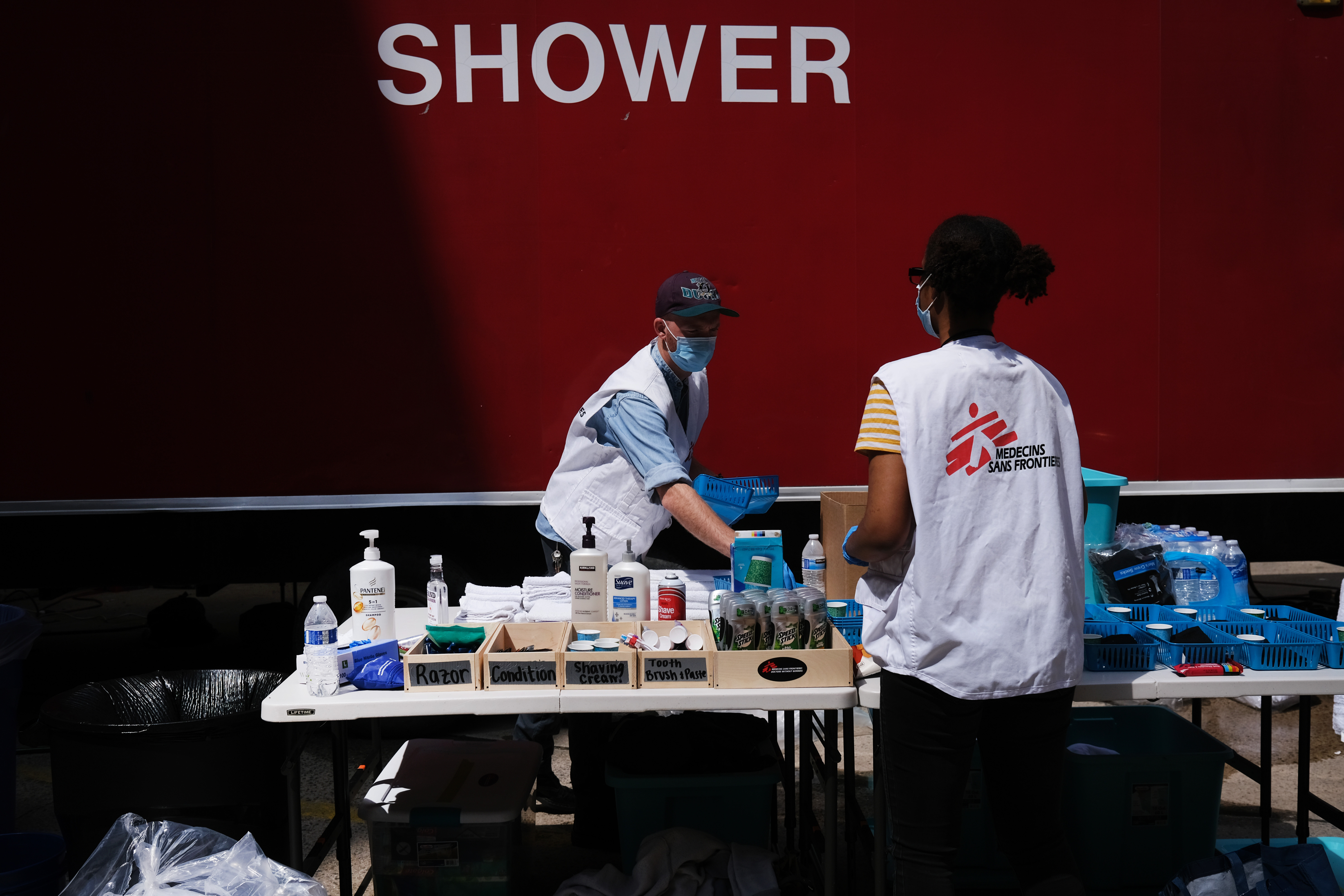 Employees prepare free toiletries at a Doctors Without Borders/Médecins Sans Frontières (MSF) temporary shower trailer in Manhattan for the homeless and other vulnerable communities on May 07, 2020 in New York City. (Photo by Spencer Platt/Getty Images)