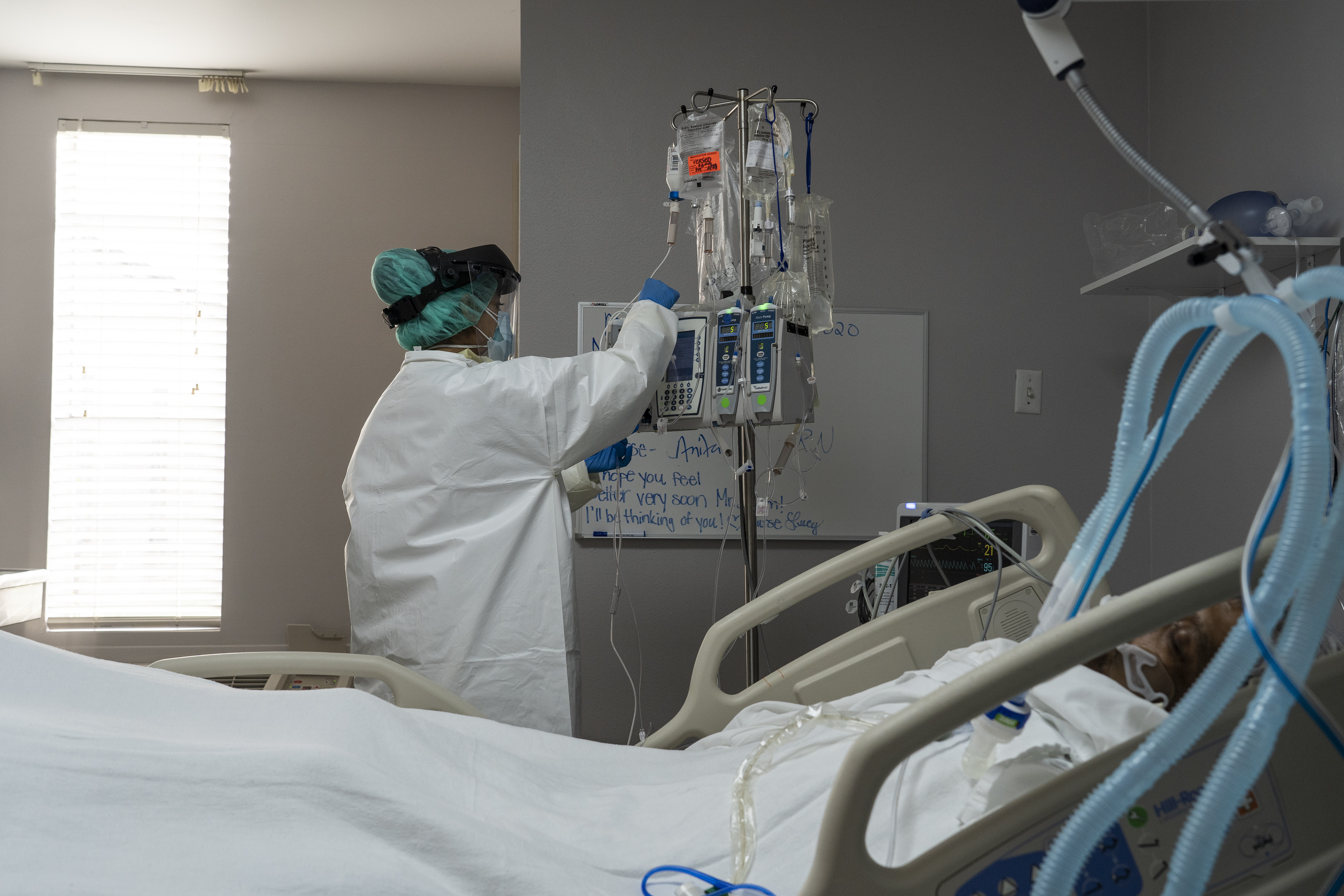 HOUSTON, TX - JUNE 30: A member of the medical staff treats a patient in the Covid-19 intensive care unit at the United Memorial Medical Center on June 30, 2020 in Houston, Texas. Covid-19 cases and hospitalizations have spiked since Texas reopened, pushing intensive-care wards to full capacity and sparking concerns about a surge in fatalities as the virus spreads. (Photo by Go Nakamura/Getty Images)