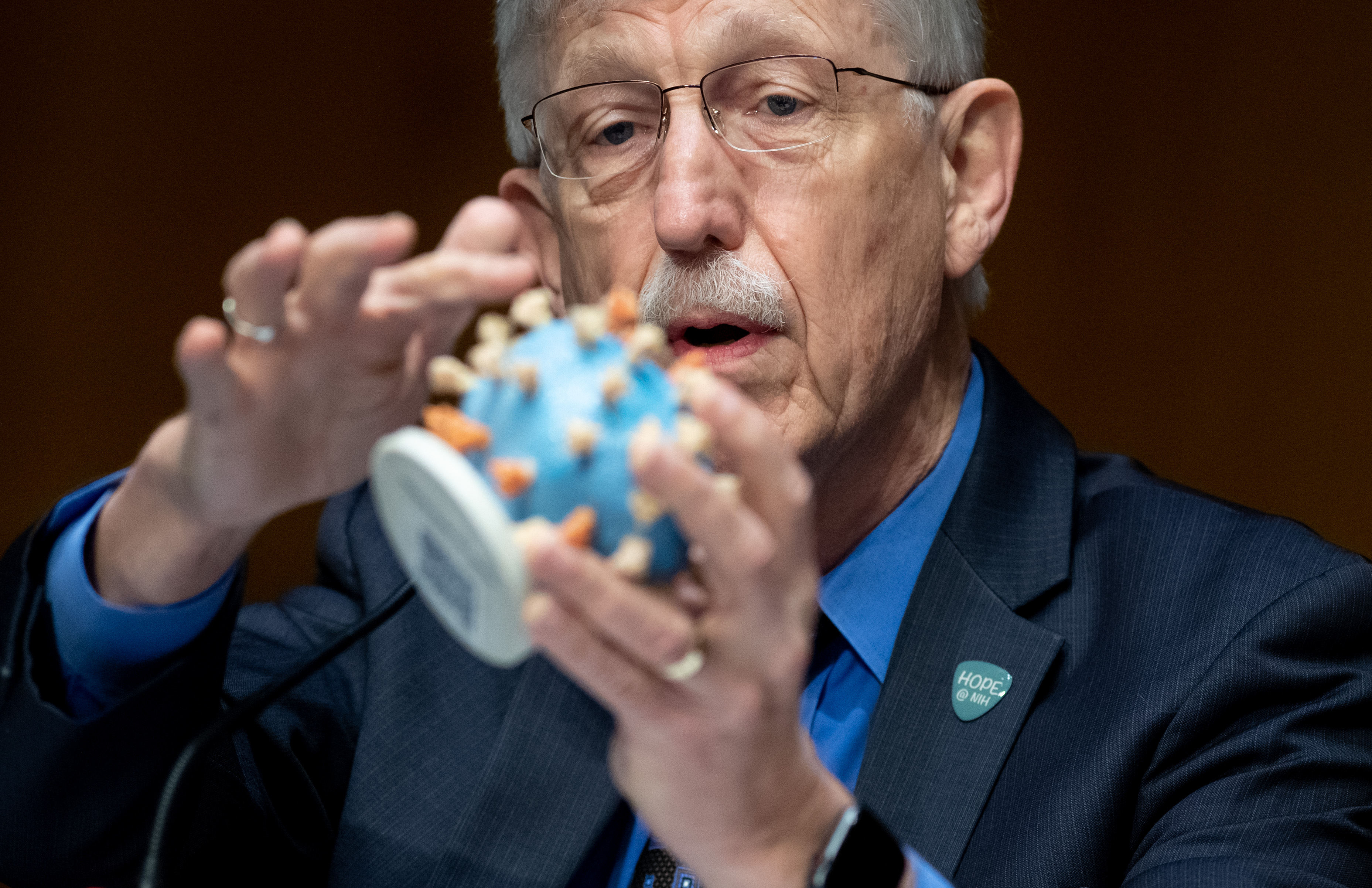 Dr. Francis Collins, director of the National Institutes of Health, holds up a model of coronavirus, during a hearing on the vaccine on July 2, 2020. (Photo: Saul Loeb-Pool/Getty Images)