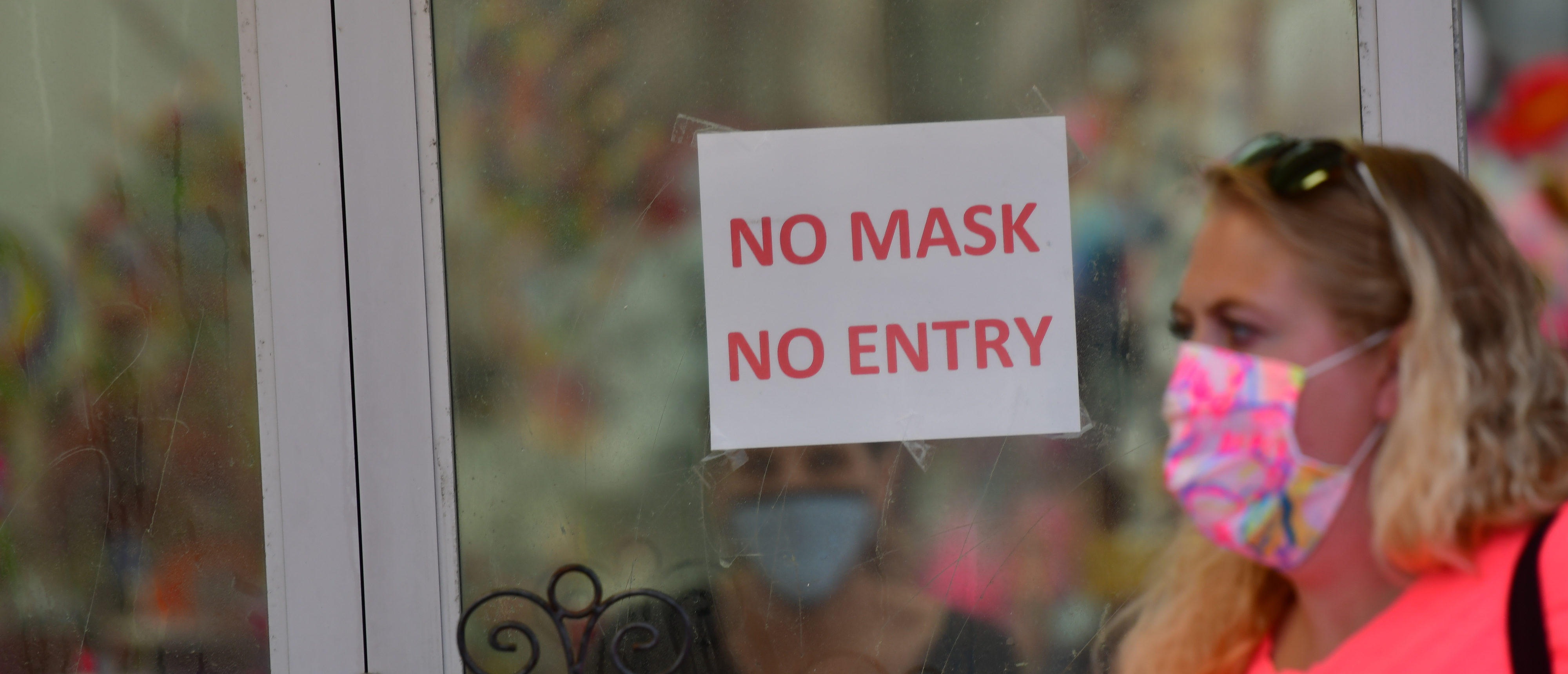 WILDWOOD, NJ - JULY 03: A woman wearing a face mask walks past a Boardwalk store with signs warning patrons of mask requirements on July 3, 2020 in Wildwood, New Jersey. New Jersey beaches have reopened for the July 4th holiday as some coronavirus restrictions have been lifted, along with casinos, amusement rides and water parks at limited capacity. (Photo by Mark Makela/Getty Images)