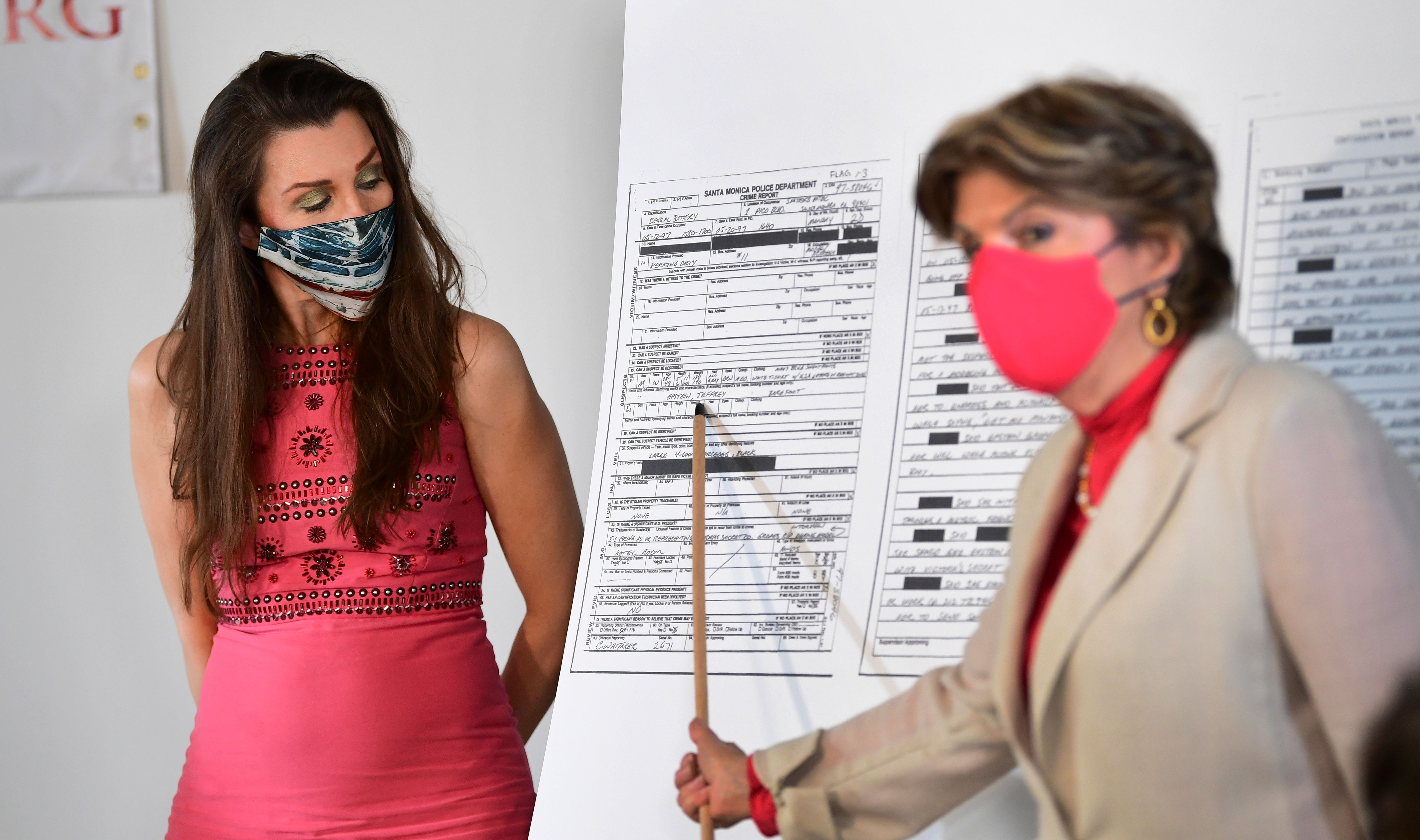 Alicia Arden, one of 16 victims of the late Jeffrey Epstein, looks on as attorney Gloria Allred points to Epstein's name on a police report Arden filed during a press conference in Los Angeles, California on July 6, 2020. - On the one-year anniversary of the arrest of Jeffrey Epstein, attorney Gloria Allred demanded an investigation into why no action was taken when her client filed a police report in 1997 alleging that Jeffrey Epstein had sexually battered her. (Photo by FREDERIC J. BROWN/AFP via Getty Images)