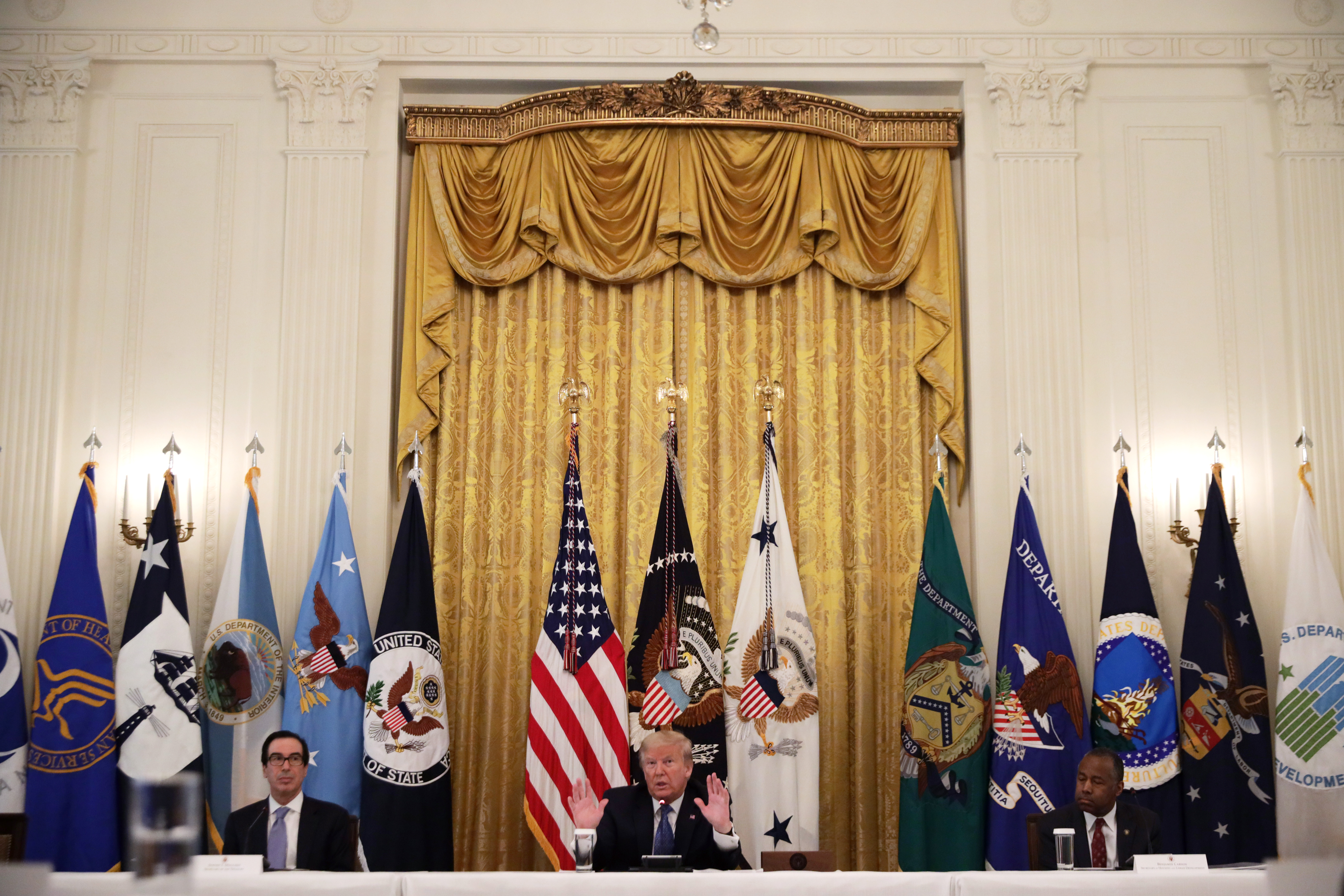 WASHINGTON, DC - MAY 19: U.S. President Donald Trump speaks as Secretary of the Treasury Steven Mnuchin and Secretary of Housing and Urban Development Ben Carson listen during a meeting with his cabinet in the East Room of the White House on May 19, 2020 in Washington, DC. Earlier in the day President Trump met with members of the Senate GOP. (Photo by Alex Wong/Getty Images)