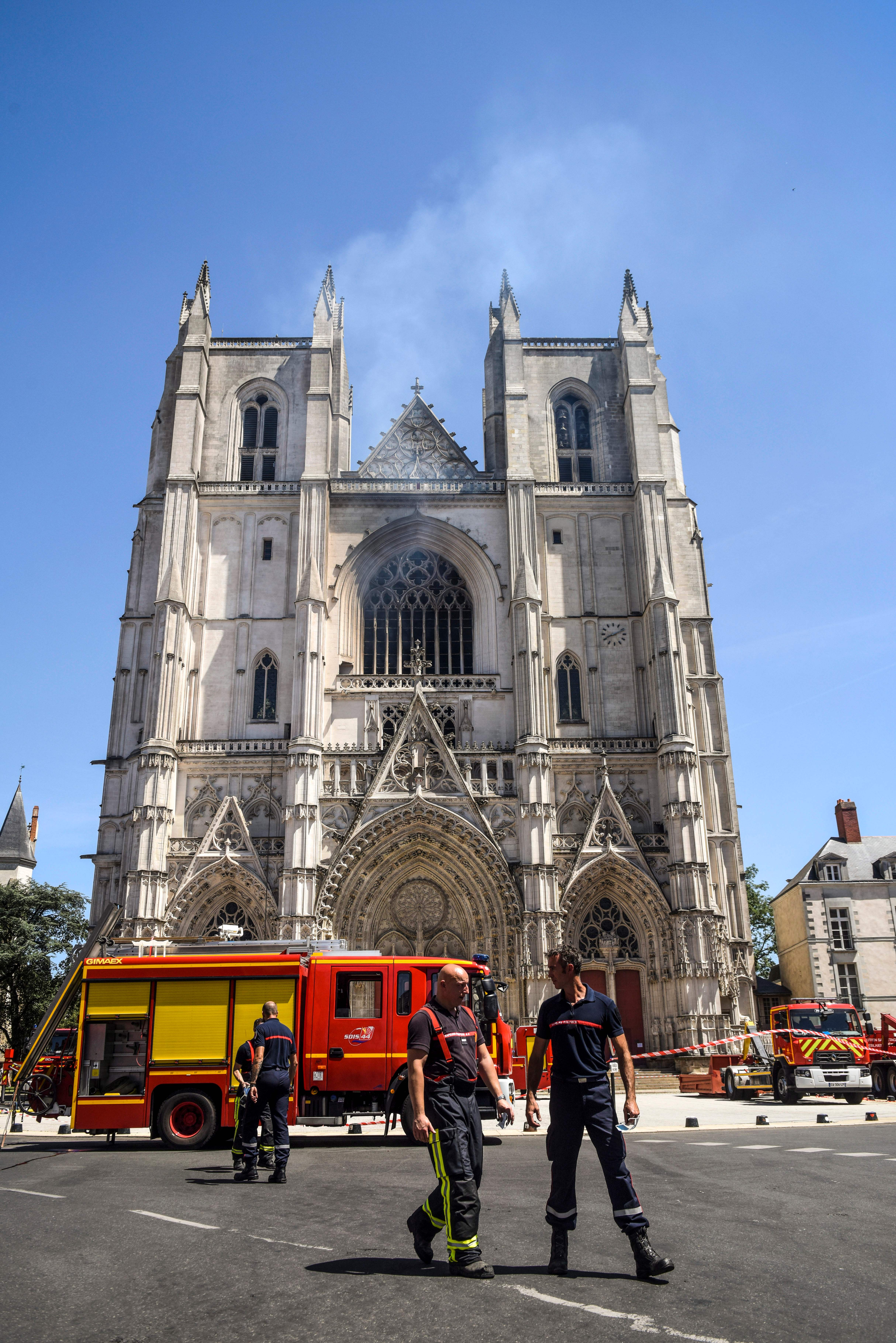 Firefighters are at work at the Cathedral of St Peter and St Paul in Nantes on July 18, 2020 after a fire ravaged parts of the gothic building before being brought under control, sparking an arson investigation and leaving Catholic officials lamenting the loss of priceless historical artefacts. (Photo by SEBASTIEN SALOM-GOMIS/AFP via Getty Images)