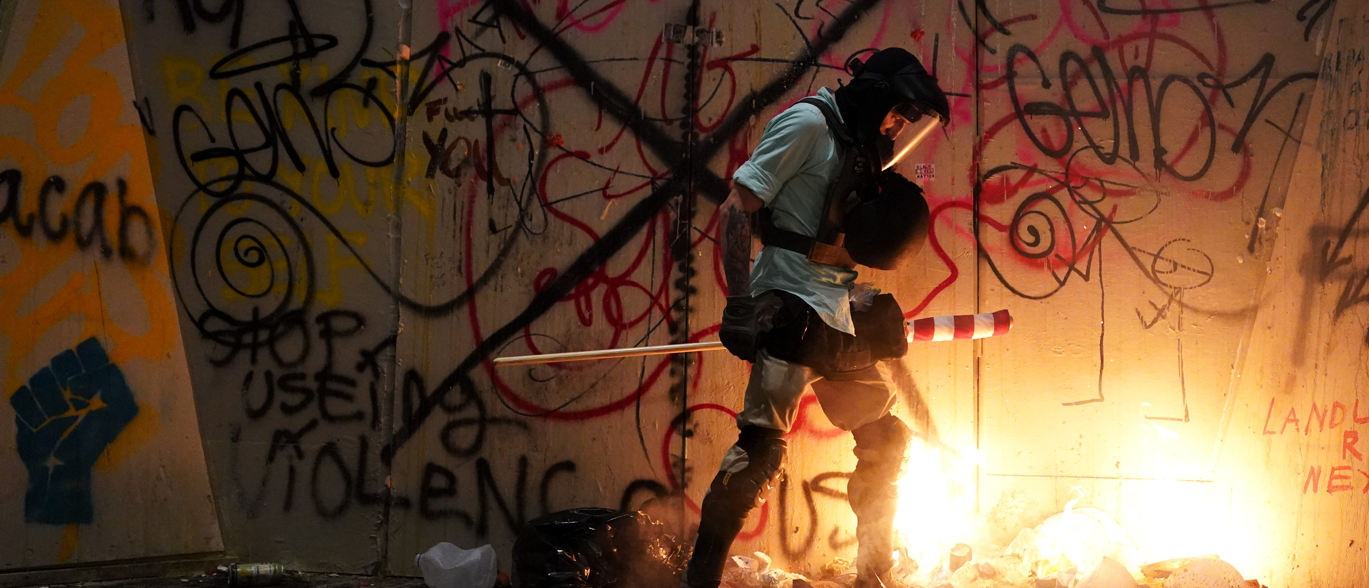 A protester attempts to stomp out a small fire during a protest at the Mark O. Hatfield U.S. Courthouse on July 21, 2020 in Portland, Oregon. Tuesday night marked 55 days of protests in Portland following the death of George Floyd in police custody. (Photo by Nathan Howard/Getty Images)