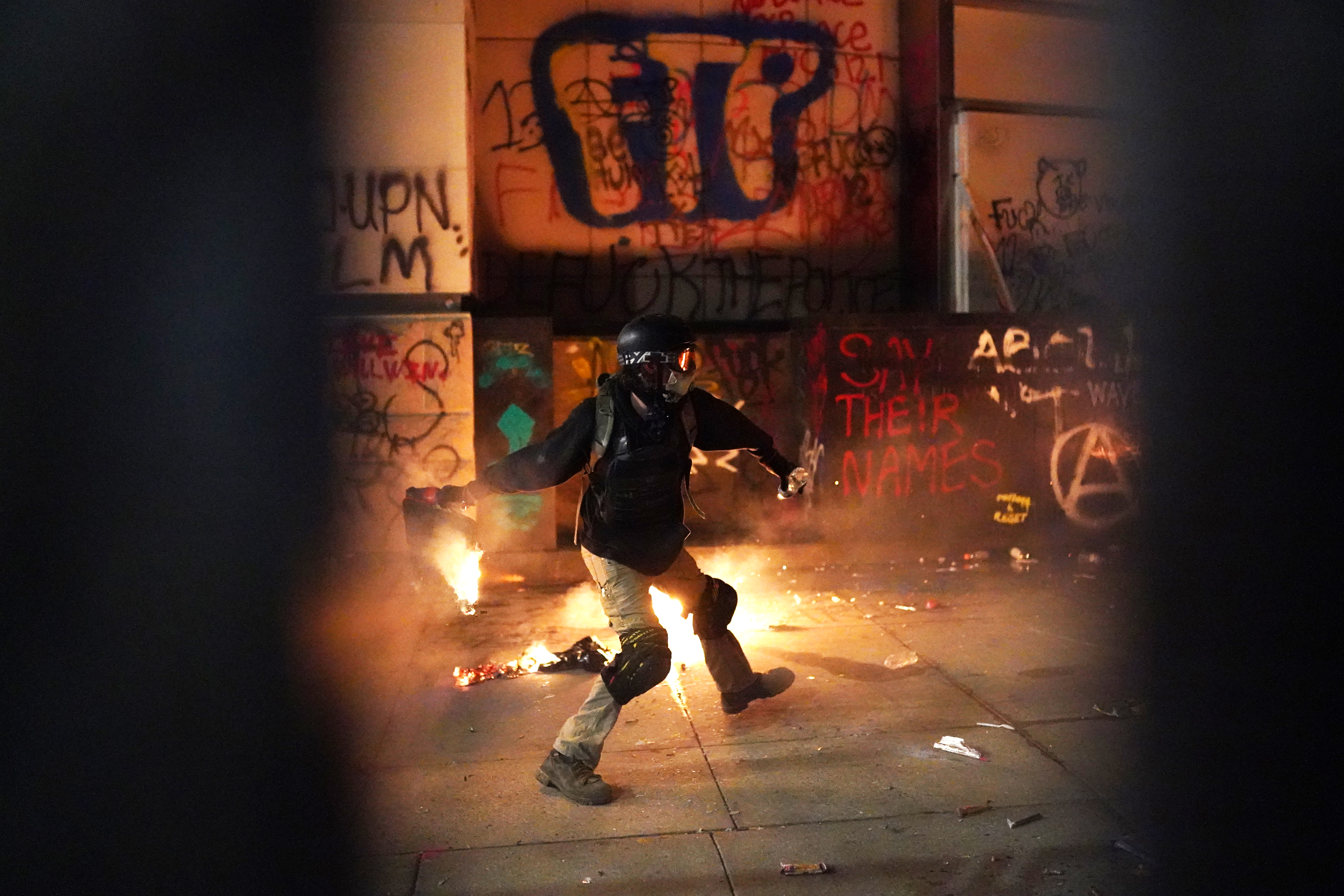A protester throws flaming trash toward the Mark O. Hatfield U.S. Courthouse after breaking through a newly-reinforced perimeter fence on July 22, 2020 in Portland, Oregon. (Photo: Nathan Howard/Getty Images)
