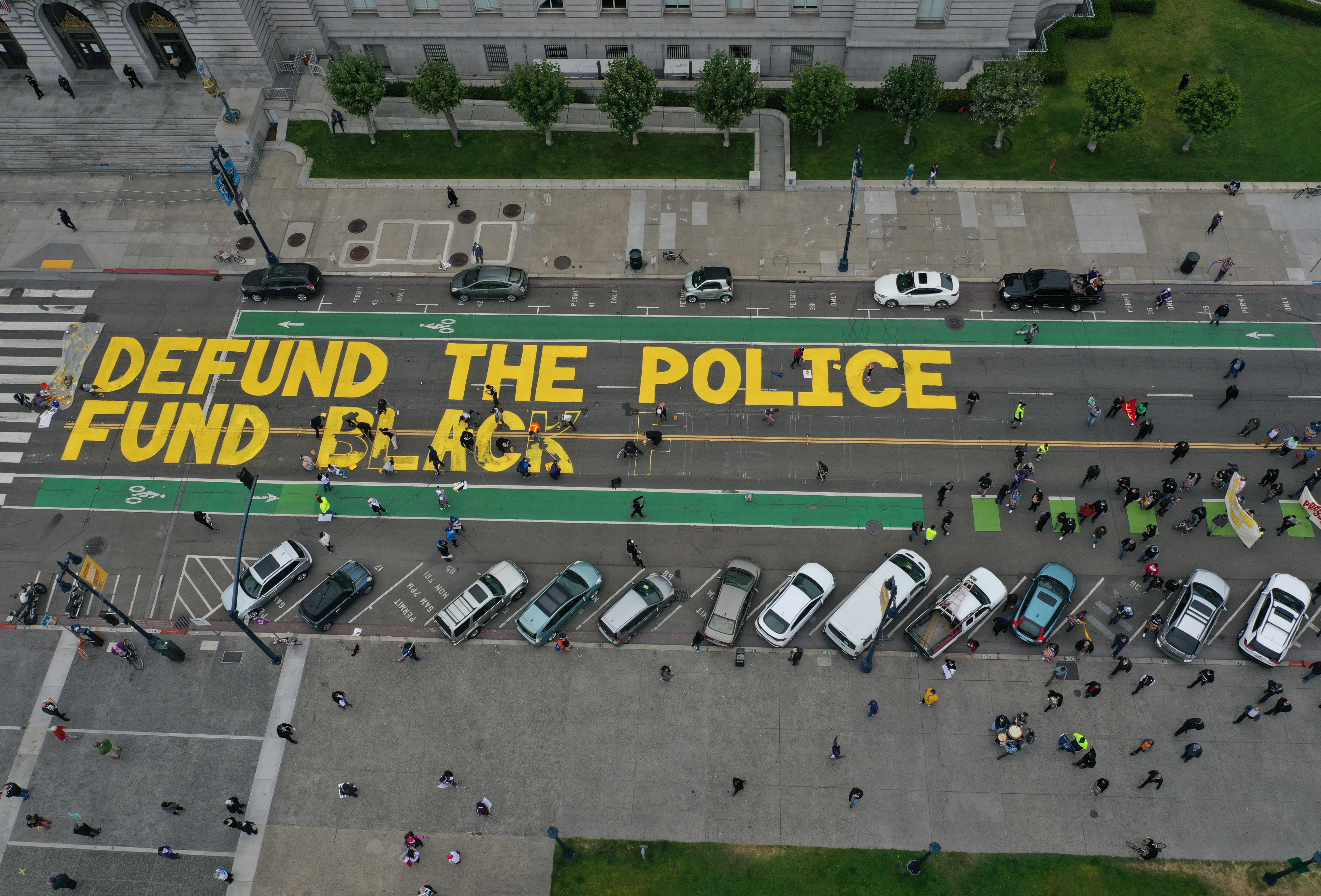 SAN FRANCISCO, CALIFORNIA - JULY 20: Protesters paint a mural that says 'defund the police' during a Strike For Black Lives demonstration outside of San Francisco City Hall on July 20, 2020 in San Francisco, California. The demonstration was part of the nationwide Strike for Black Lives effort which is calling for higher wages, better jobs, and Unions to help workers build economic power. (Justin Sullivan/Getty Images)