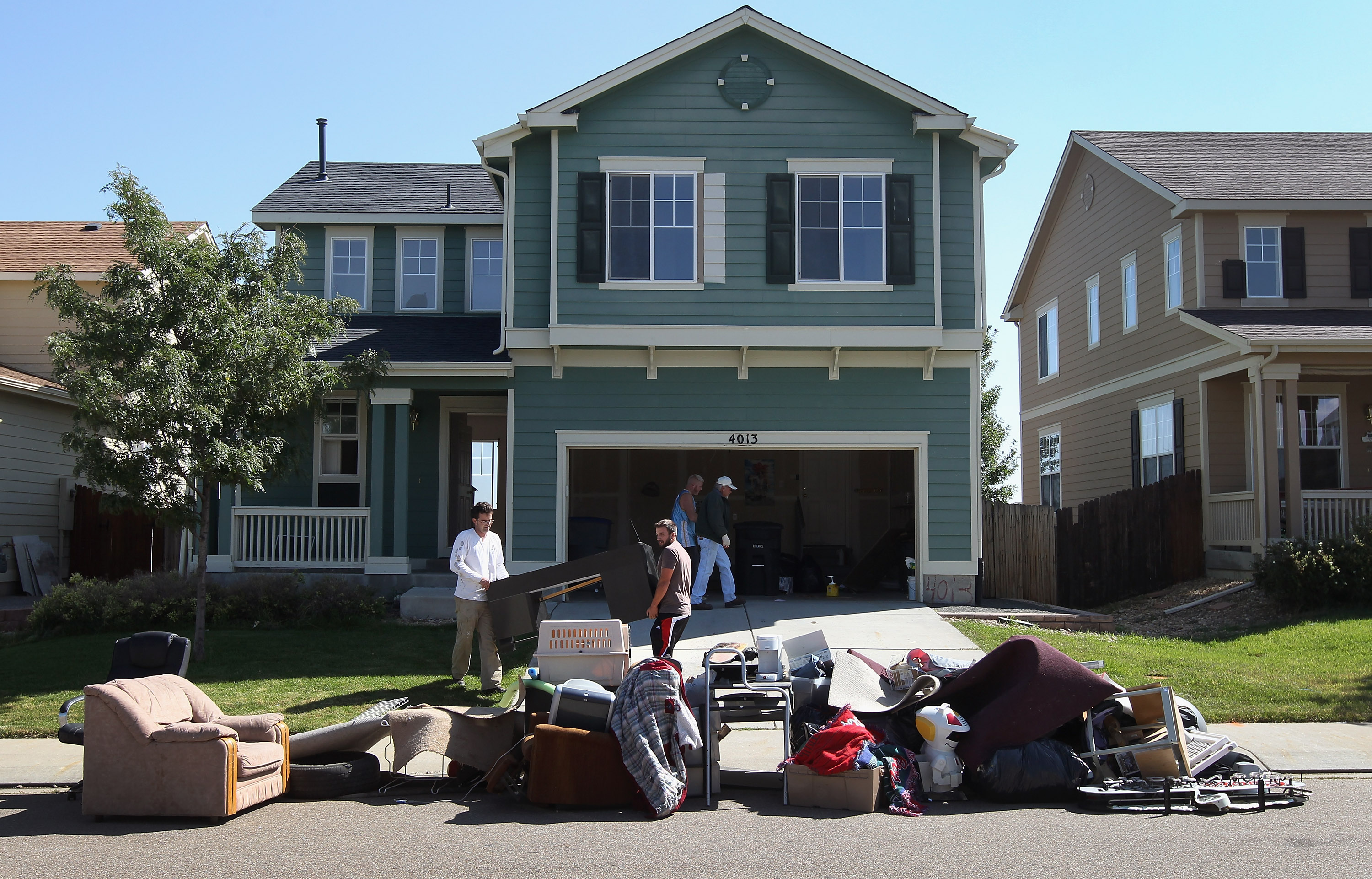 LONGMONT, CO - SEPTEMBER 21: An eviction team removes furniture during a home foreclosure on September 21, 2011 in Longmont, Colorado. The family had already moved out of the four-bedroom house, leaving some furniture to be removed to the street after the sheriff's department served the court order for the eviction. Although sales of previously owned homes have risen nationally, the glut of foreclosures is expected to keep the rise in home values below the rate of inflation for years. (Photo by John Moore/Getty Images)