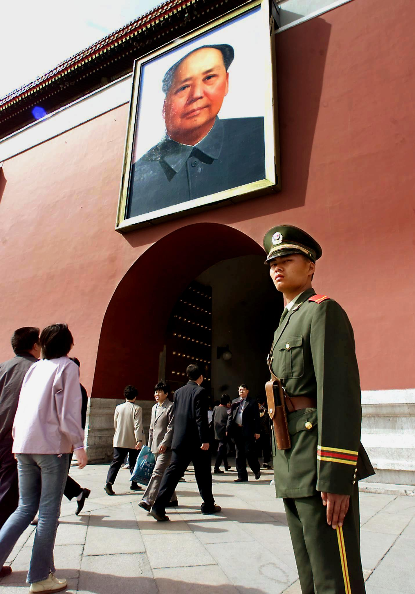 A policeman stands guard in front of the Tiananmen Gate with the portrait of Mao Zedong in Beijing 24 April 2001, as police tightened security around Tiananmen Square to prevent followers of the outlawed Falungong spiritual group from protesting and possible self-immolation on the eve of the anniversary of the 25 April, 1999 demonstration. (GOH CHAI HIN/AFP via Getty Images)