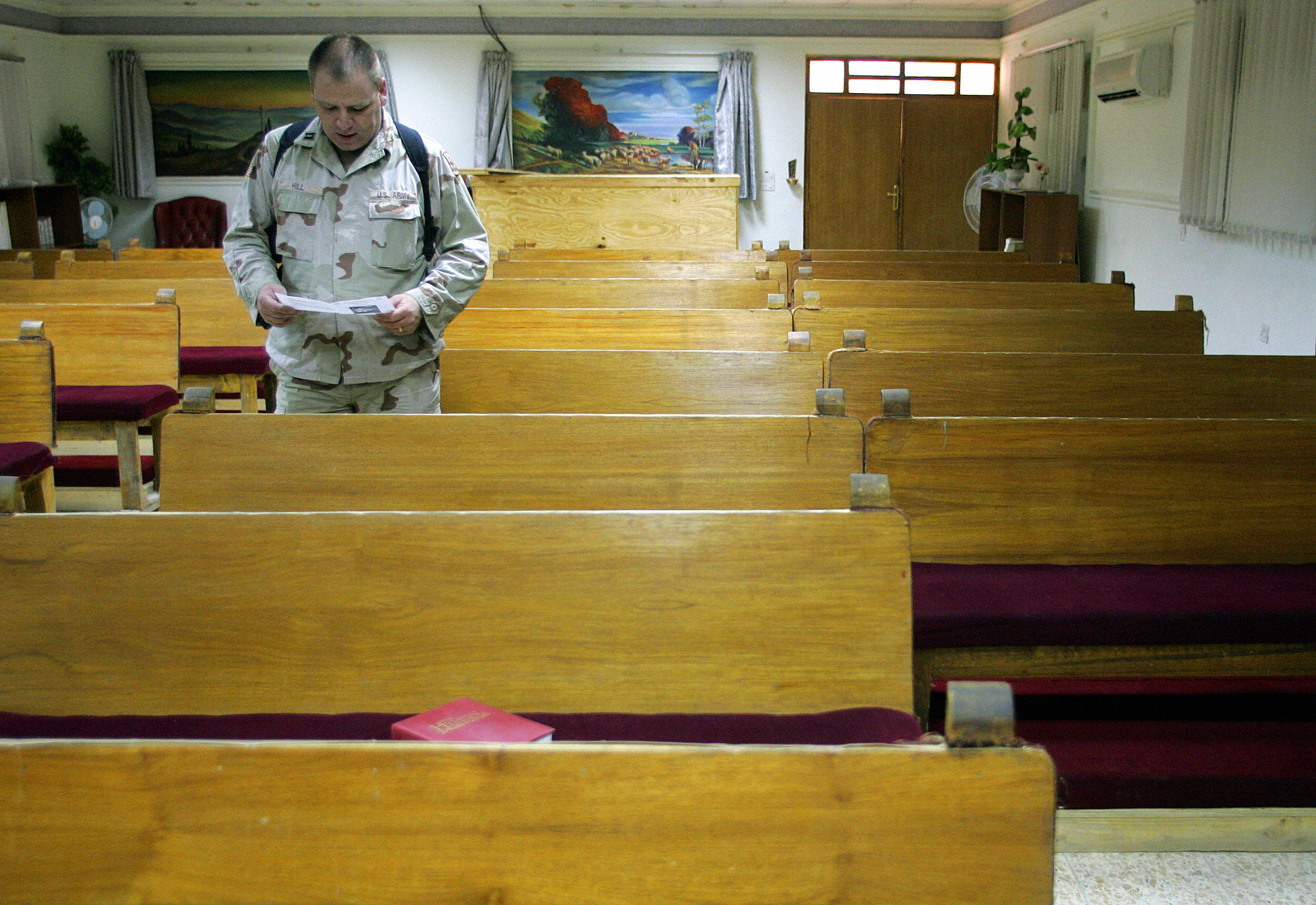 A US soldier of the 3rd Infantry Division prays during a weekly worship service at a chapel in Camp Falcon, southern Baghdad, 20 August 2005. (Photo credit should read LIU JIN/AFP via Getty Images)