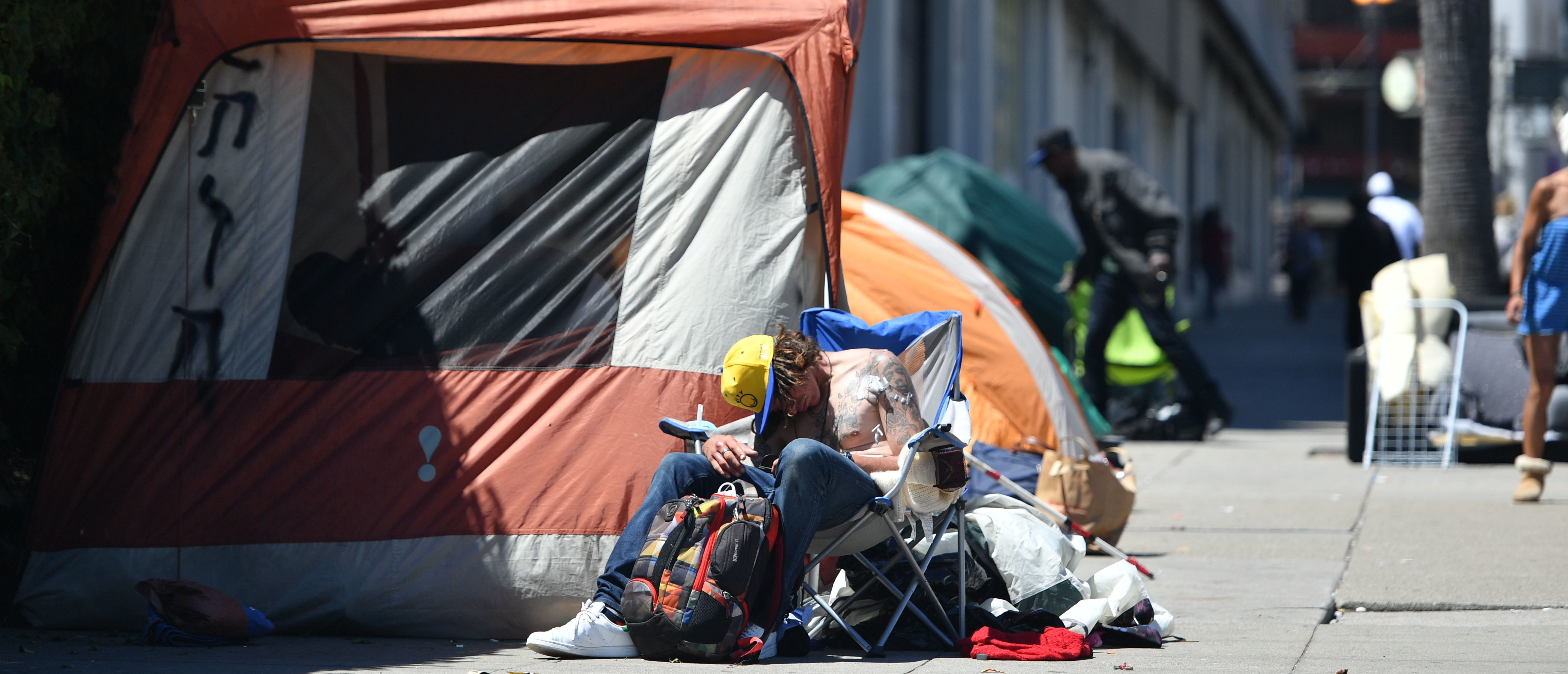 A homeless man sleeps in front of his tent along Van Ness Avenue in downtown San Francisco, California on June, 27, 2016. Homelessness is on the rise in the city irking residents and bringing the problem under a spotlight. (JOSH EDELSON/AFP via Getty Images)