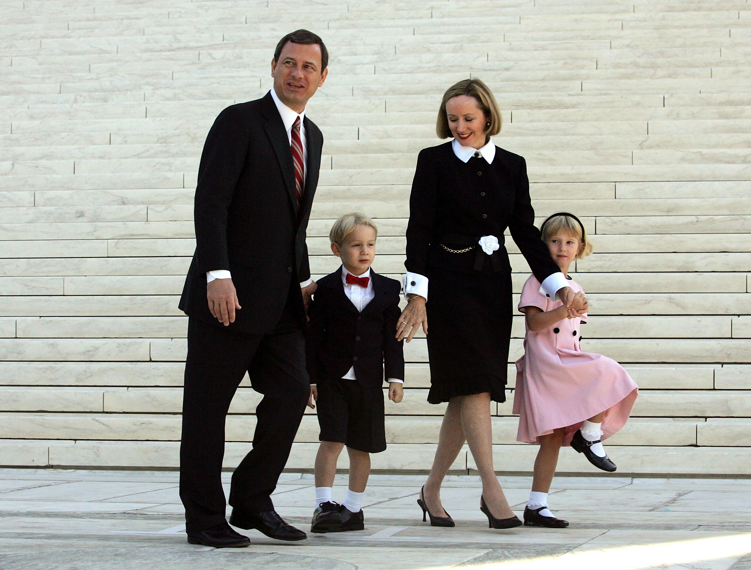 Chief Justice John Roberts walks with his wife Jane Roberts and their children Jack Roberts and Josie Roberts at the Supreme Court after he took the Supreme Court bench for the first time October 3, 2005 in Washington, DC. Roberts replaced William H. Rehnquist as the new chief Justice. (Photo by Joe Raedle/Getty Images)