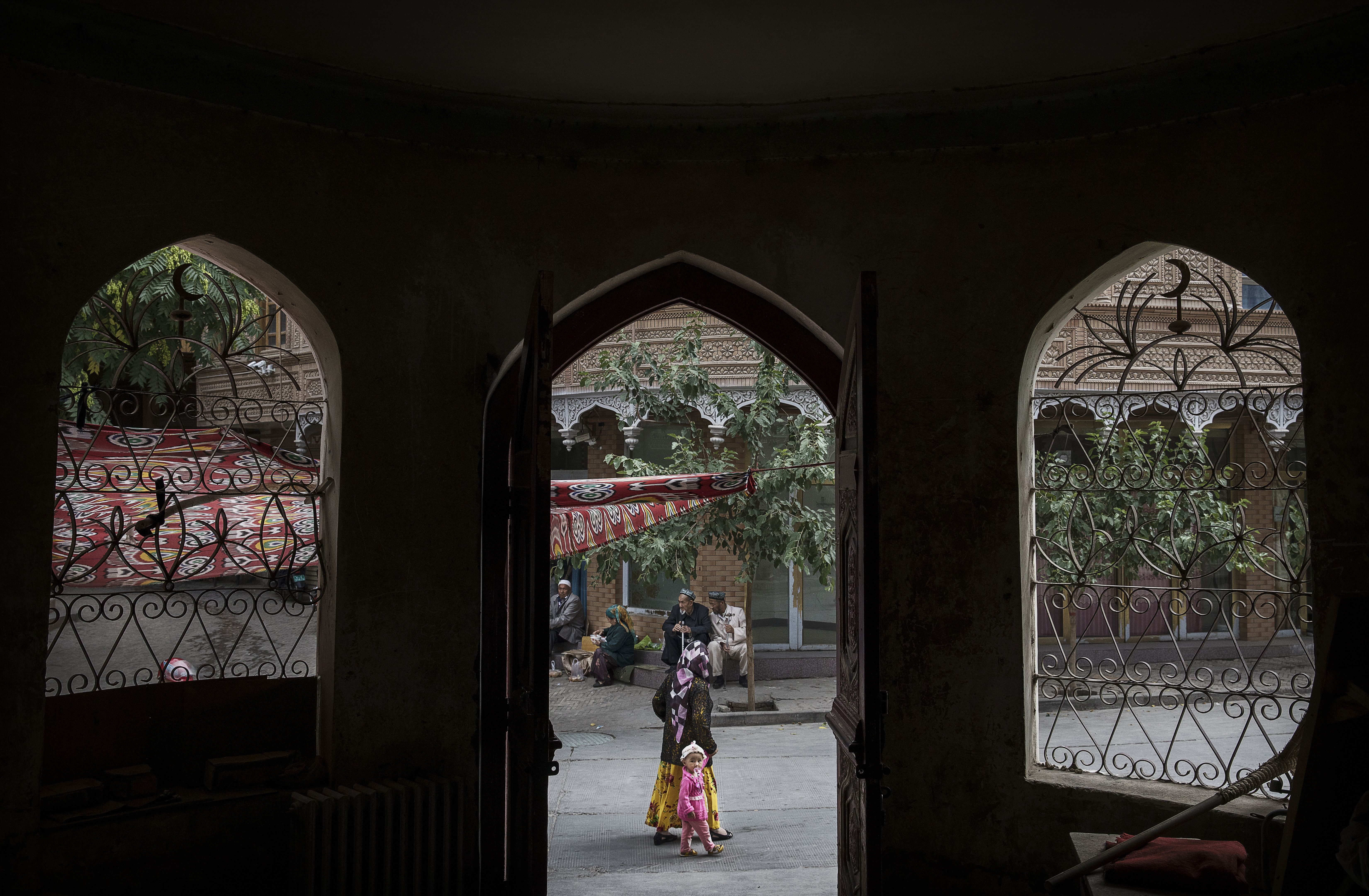 An ethnic Uyghur woman walks by the closed Islamic school on July 1, 2017 in the old town of Kashgar, in the far western Xinjiang province, China. Kashgar has long been considered the cultural heart of Xinjiang for the province's nearly 10 million Muslim Uyghurs. (Photo by Kevin Frayer/Getty Images)