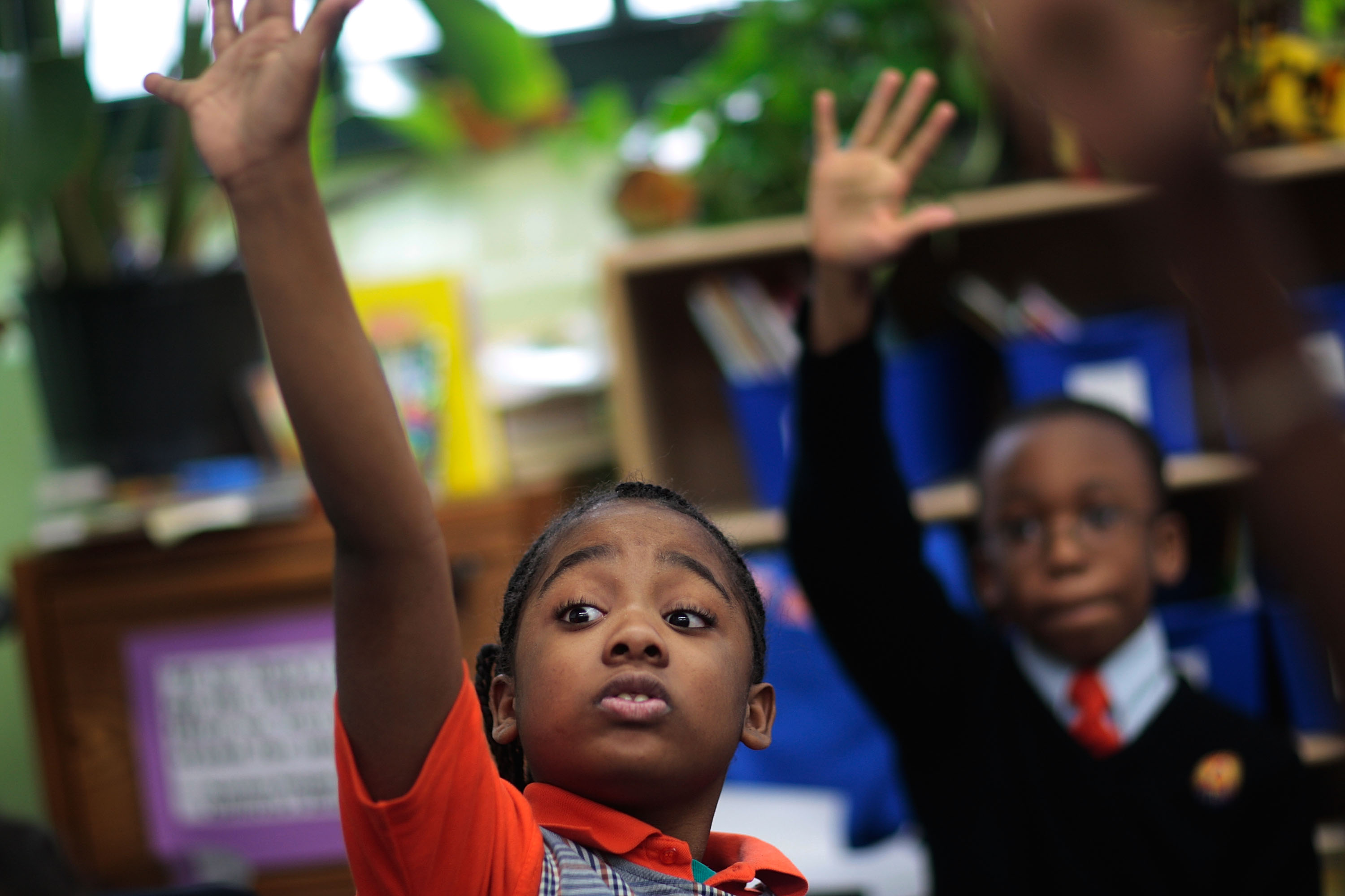 NEW YORK - MARCH 30: Third grade students Tyler Smalls (L) and Sekou Cisse raise their hands in reading comprehension class at Harlem Success Academy, a free, public elementary charter school March 30, 2009 in the Harlem neighborhood of New York City. All students at the charter school are required to wear uniforms. (Photo by Chris Hondros/Getty Images)