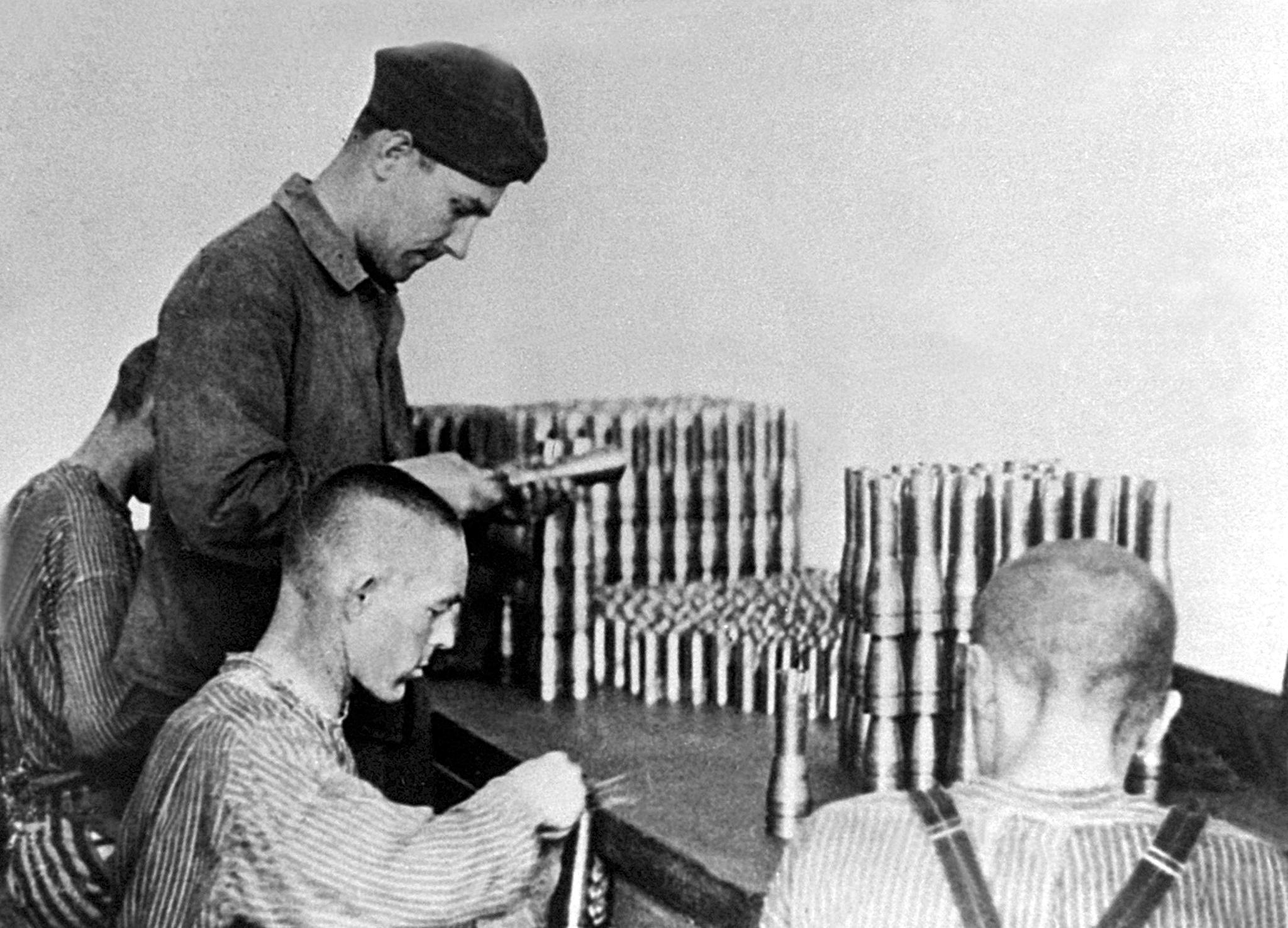 This undated picture shows prisoners of the Dachau concentration camp producing parts for weapons. Germany's chief negotiator on compensation for Nazi-era forced and slave laborers, Otto Graf Lambsdorff, said 22 May 2001 that the legal conditions were in place for payments to begin. / AFP PHOTO / DPA (Photo credit should read /DPA/AFP via Getty Images)