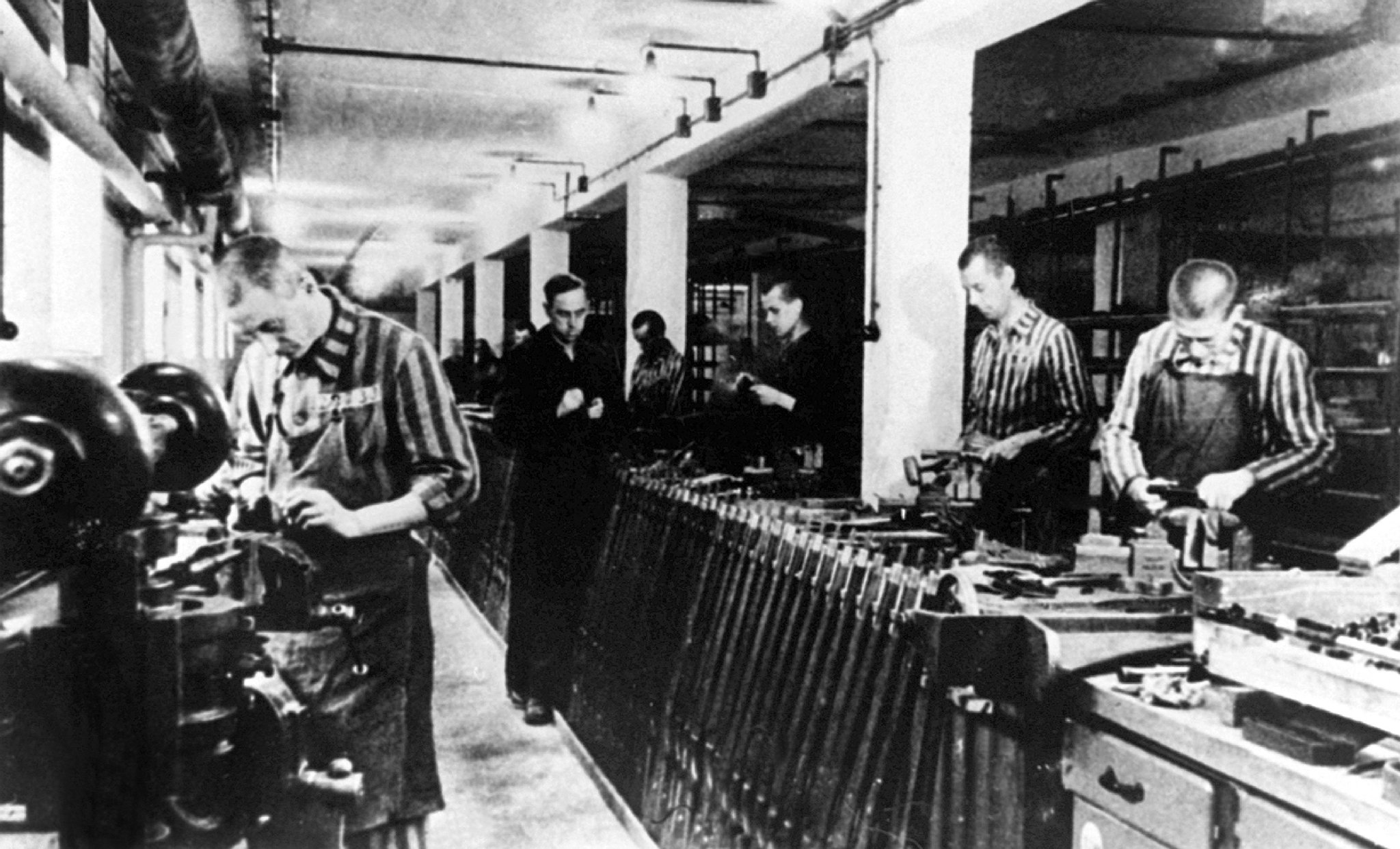 Undated file picture showing slave labourer producing weapons in the Nazi concentration camp in Dachau. Germany and the United States have reached an agreement on compensation for former Nazi slaves, a spokesman for German government negotiator Otto Lambsdorff said 14 December 1999. It was not said if lawyers for the victims had joined the accord, nor how much was now being offered. Lambsdorff announced earlier that the Germany was ready to increase its compensation offer to speed up negotiations. B/W ONLY / AFP PHOTO / DPA (Photo credit should read /DPA/AFP via Getty Images)