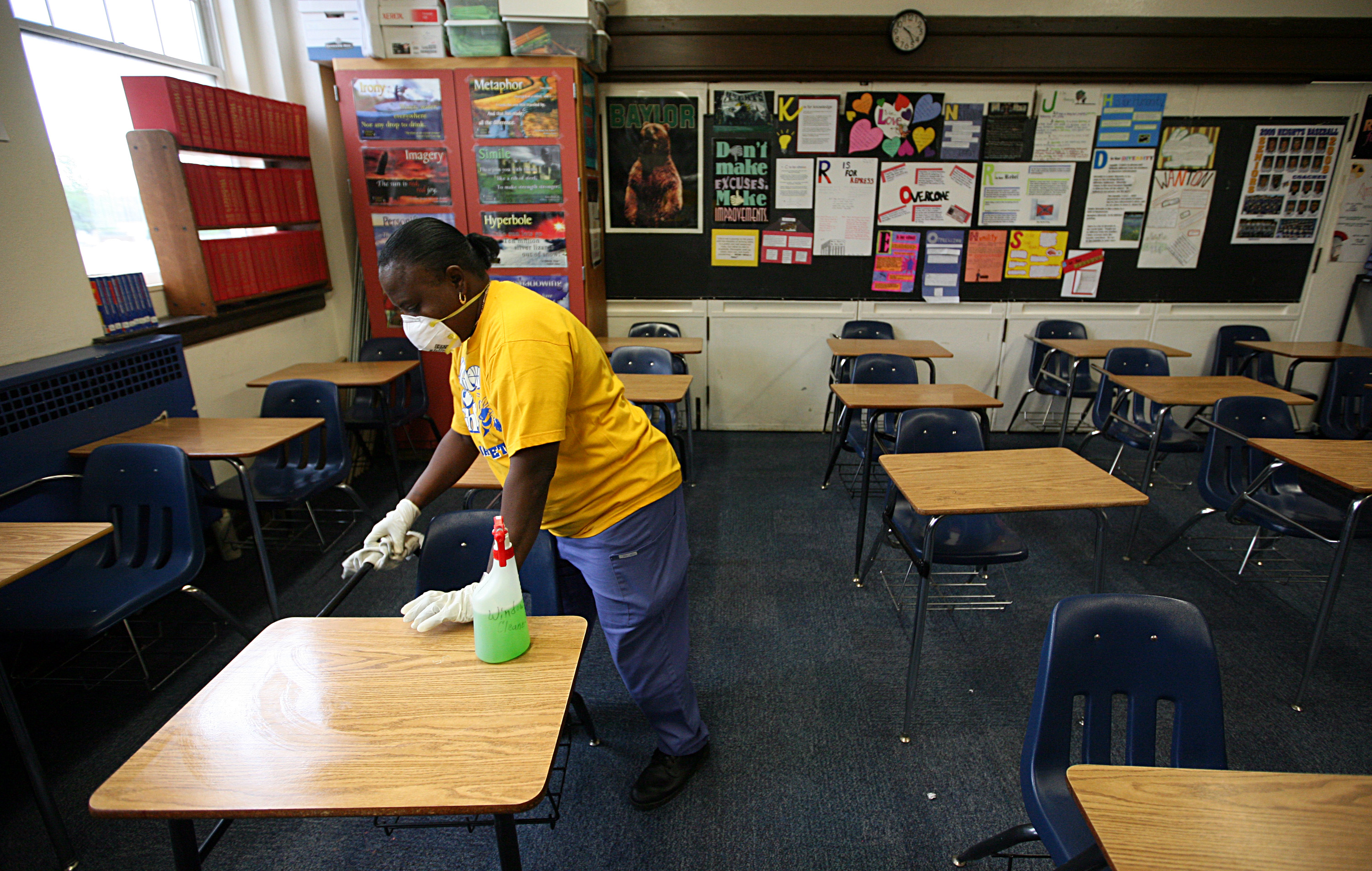 FORT WORTH - APRIL 30: Fort Worth Independent School District custodian Necie Homer wipes down a classroom with disinfectant in an effort to stop the spread of the swine flu virus at Arlington Heights High School on April 30, 2009 in Fort Worth, Texas. FWISD officials closed all schools in Fort Worth late on April 29 in an effort to stop the spread of the virus. (Photo by Tom Pennington/Getty Images)