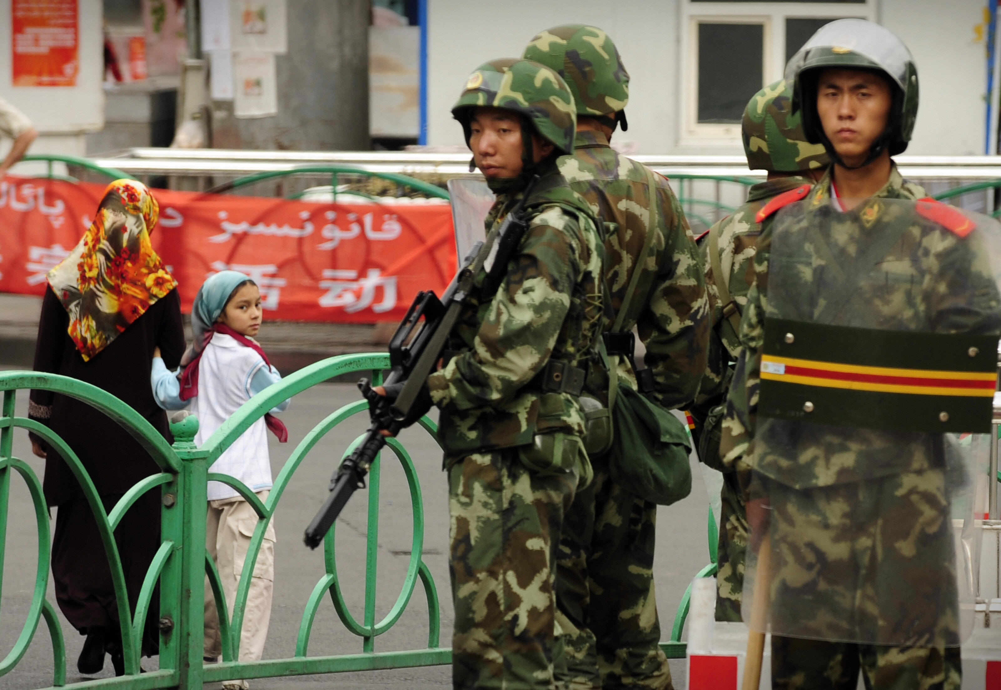 Chinese paramilitary policemen stand guard on a street in the Uighur district of Urumqi city, in China's Xinjiang region, on July 14, 2009. A mosque was closed and many businesses were shuttered a day after police shot dead two Muslim Uighurs, as ethnic tensions simmered in China's restive Urumqi city. (PETER PARKS/AFP via Getty Images)