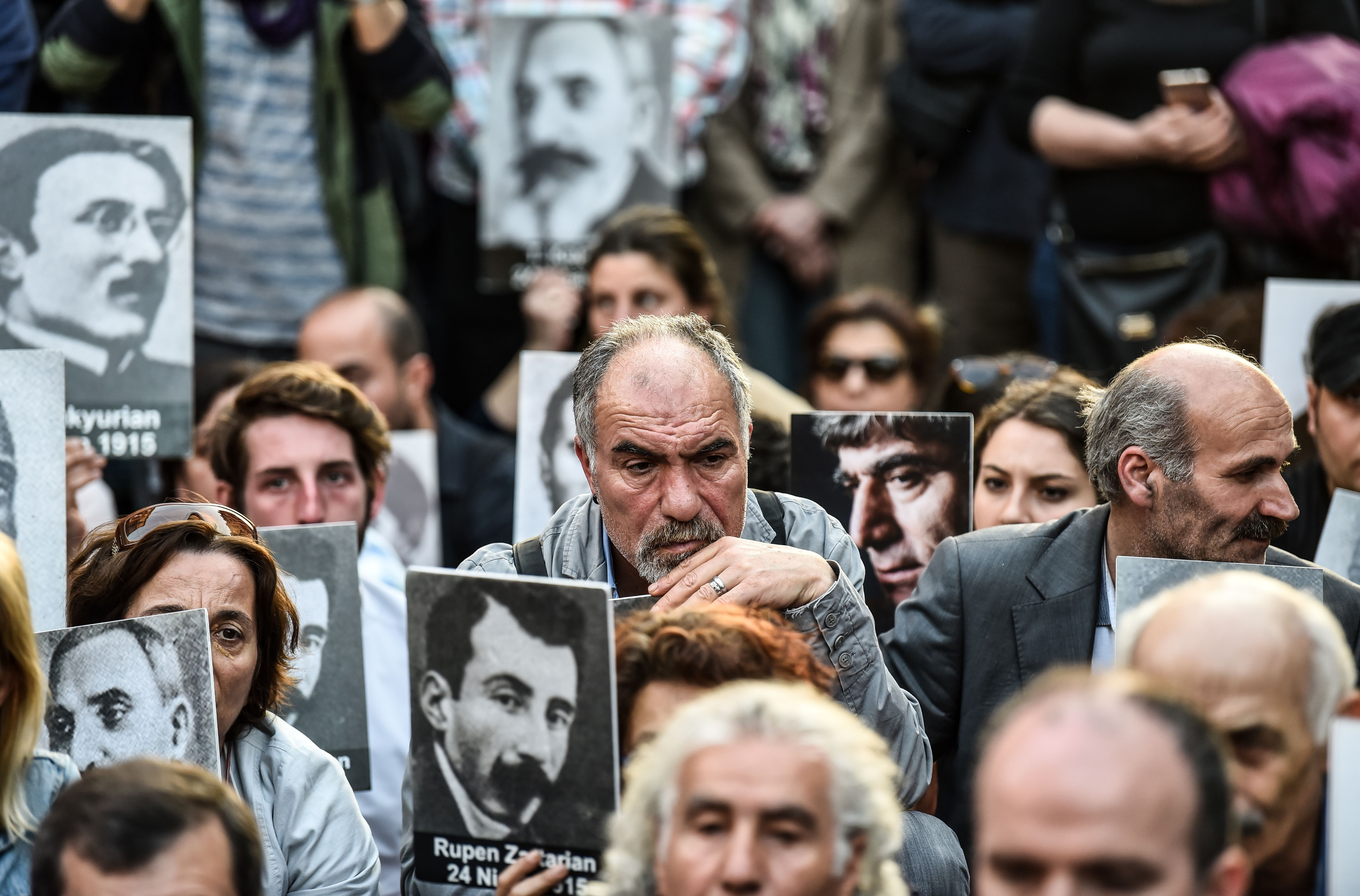 People hold portraits of Armenian intellectuals - who were detained and deported in 1915 - during a rally on Istiklal Avenue in Istanbul on April 24, 2018, held to commemorate the 103nd anniversary of the 1915 mass killing of Armenians in the Ottoman Empire. ( BULENT KILIC/AFP via Getty Images)