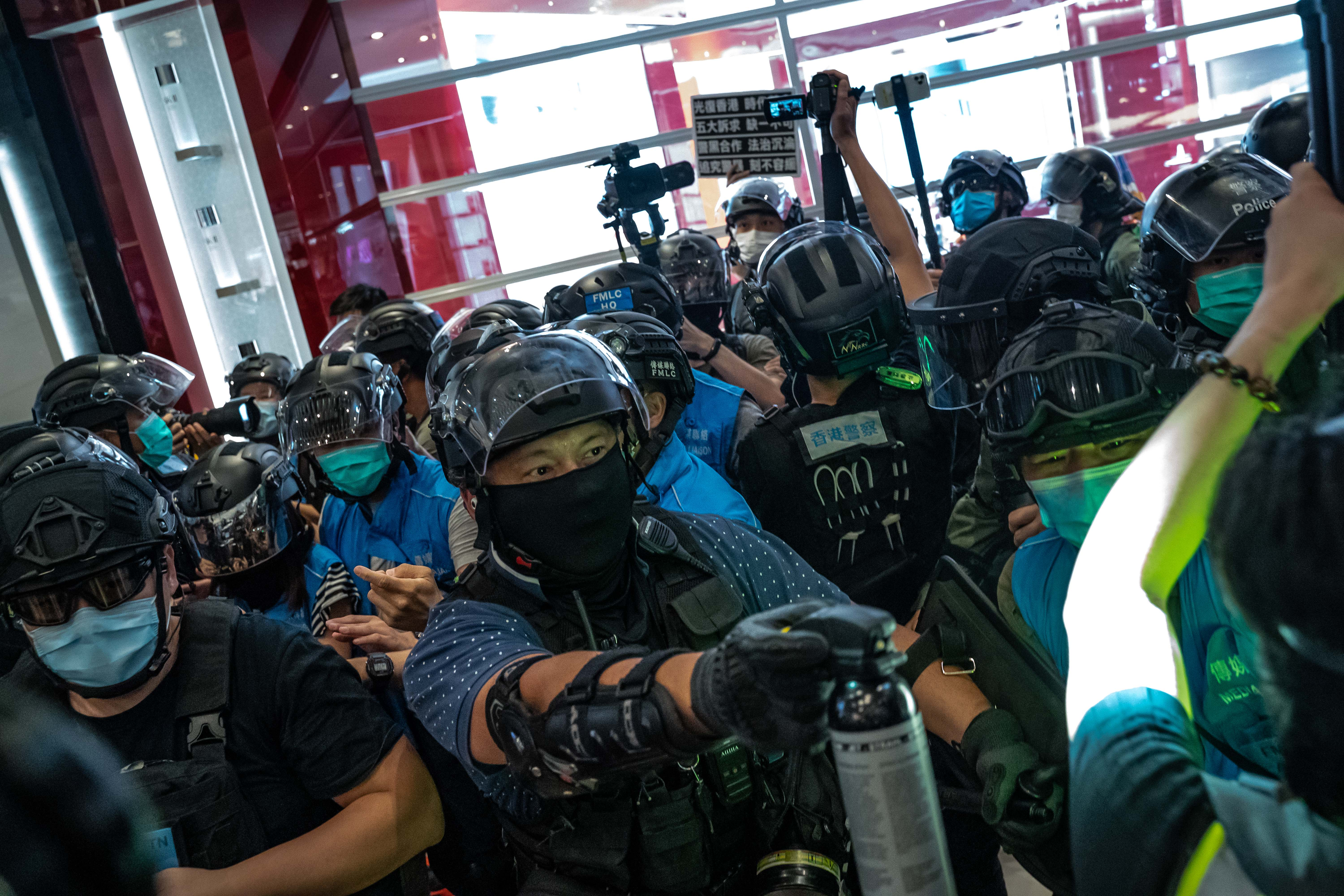 HONG KONG, CHINA - JULY 21: A protester holds up a placard as riot police surround him inside a shopping mall during a rally on July 21, 2020 in Hong Kong, China. (Photo by Anthony Kwan/Getty Images)