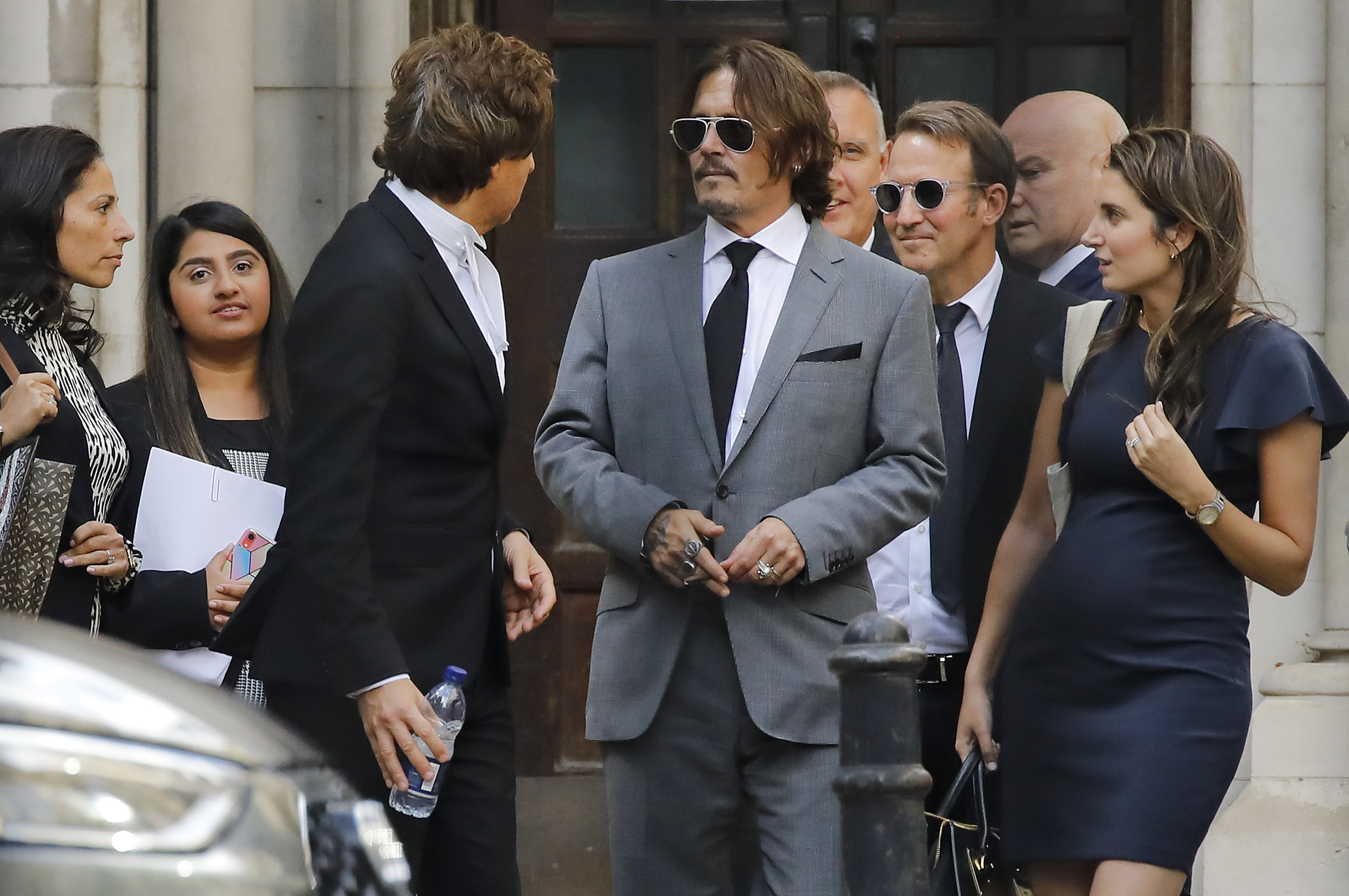 """US actor Johnny Depp (C) leaves after the fifth day of his libel trial against News Group Newspapers (NGN), at the High Court in London, on July 13, 2020. - Depp is suing the publishers of The Sun and the author of the article for the claims that called him a """"wife-beater"""" in April 2018. (Photo by TOLGA AKMEN/AFP via Getty Images)"""