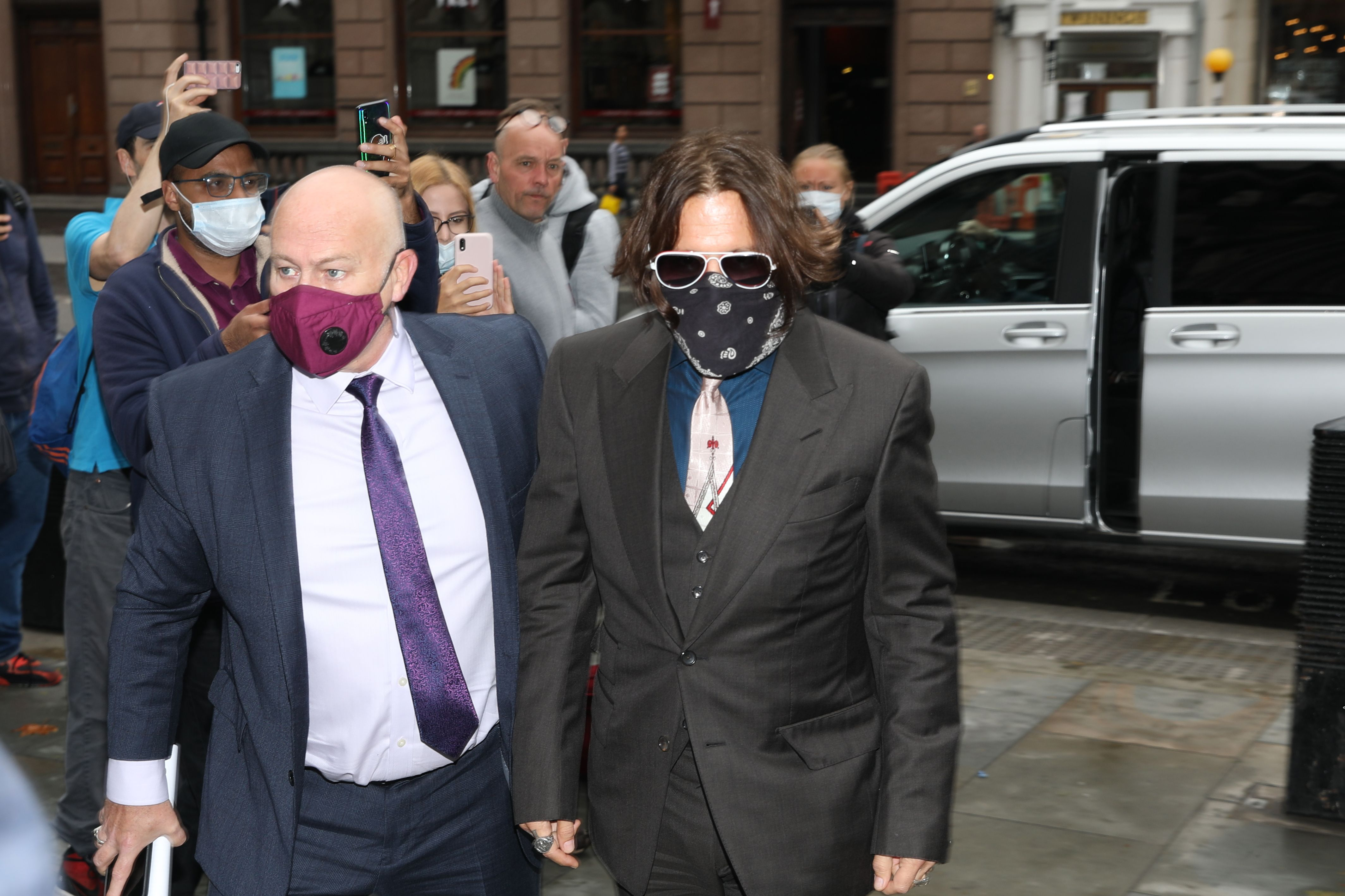 """US actor Johnny Depp (C), wearing a face mask or covering due to the COVID-19 pandemic, arrives on the second day of his libel trial against News Group Newspapers (NGN), at the High Court in London, on July 8, 2020. - Depp is suing the publishers of The Sun and the author of the article for the claims that called him a """"wife-beater"""" in April 2018. (Photo by ISABEL INFANTES/AFP via Getty Images)"""