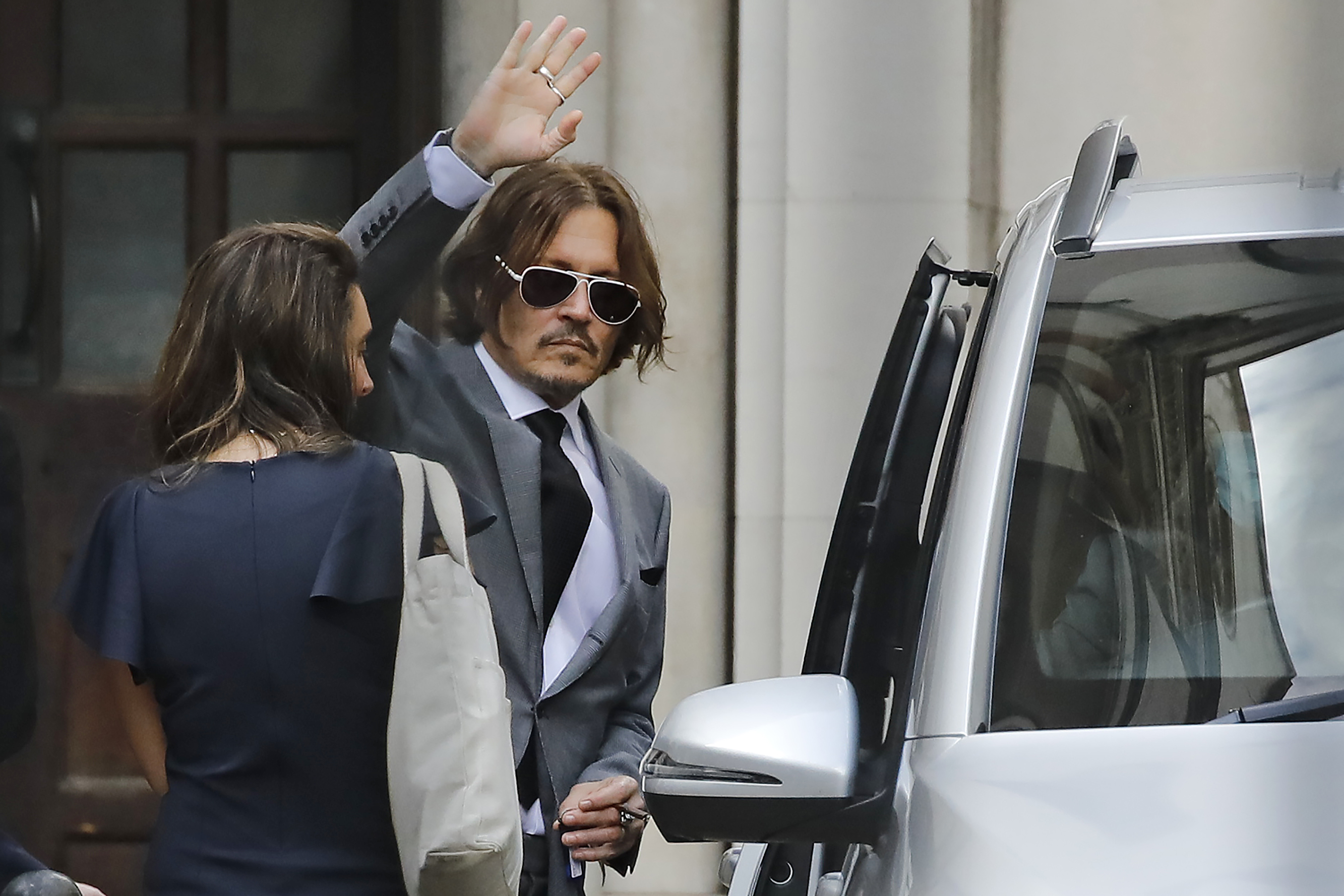 """US actor Johnny Depp waves as he leaves after the fifth day of his libel trial against News Group Newspapers (NGN), at the High Court in London, on July 13, 2020. - Depp is suing the publishers of The Sun and the author of the article for the claims that called him a """"wife-beater"""" in April 2018. (Photo by TOLGA AKMEN/AFP via Getty Images)"""