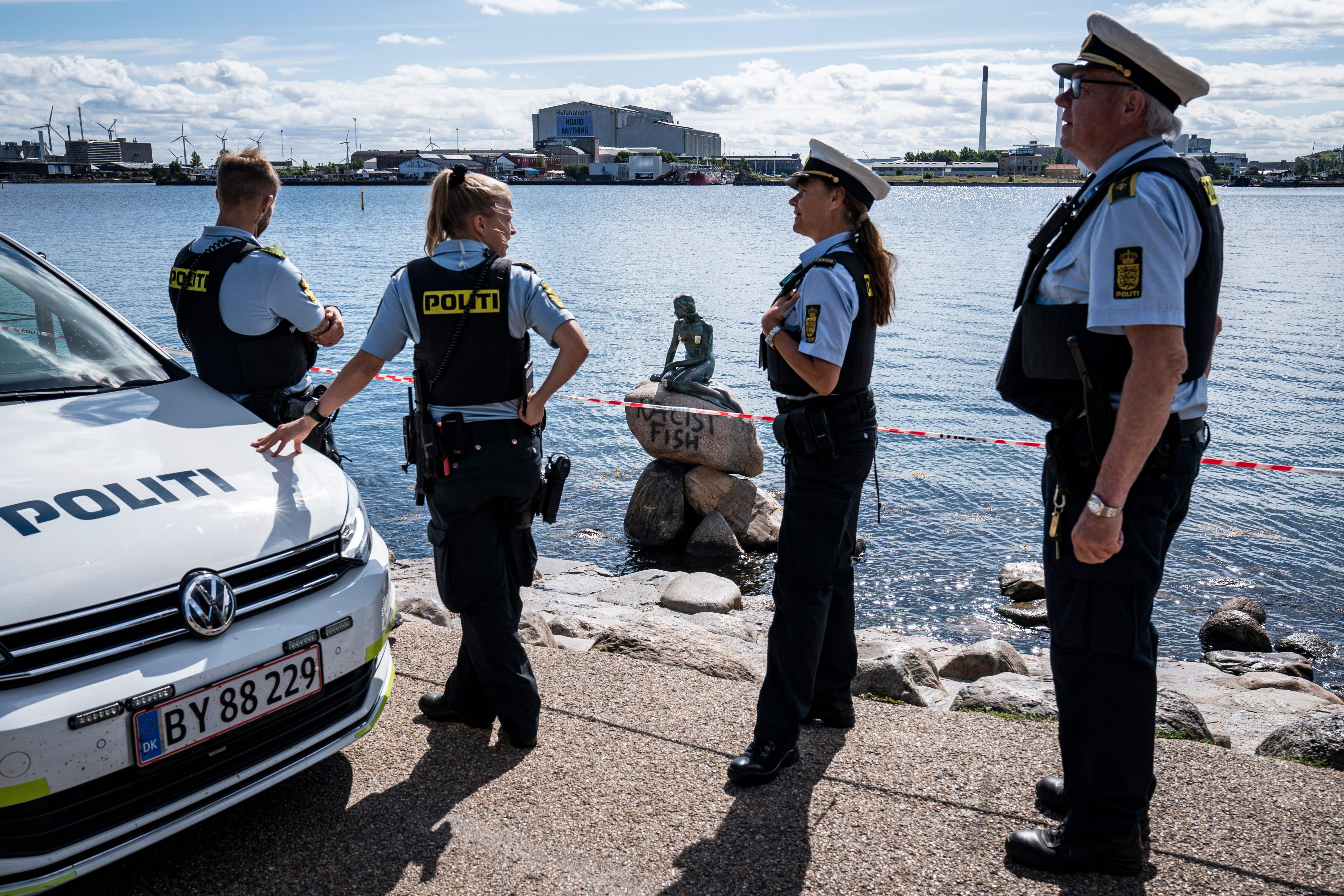 "Policemen stand on July 3, 2020 in front of the ""Little Mermaid"" sculpture after it has been vandalised in Copenhagen. (Photo by NIELS CHRISTIAN VILMANN/Ritzau Scanpix/AFP via Getty Images)"