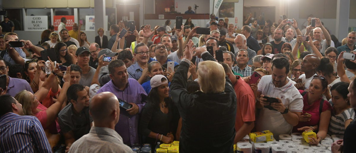 TOPSHOT - US President Donald Trump throws a paper towel roll as he visits the Cavalry Chapel in Guaynabo, Puerto Rico on October 3, 2017. Nearly two weeks after Hurricane Maria thrashed through the US territory, much of the islands remains short of food and without access to power or drinking water. / AFP PHOTO / MANDEL NGAN (Photo credit should read MANDEL NGAN/AFP via Getty Images)